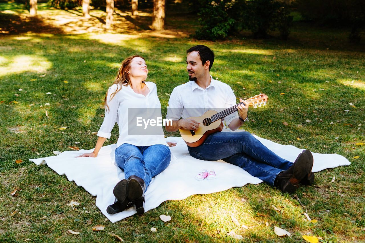 two people, music, musical instrument, couple - relationship, young men, men, heterosexual couple, young adult, string instrument, full length, real people, casual clothing, togetherness, guitar, sitting, plant, lifestyles, leisure activity, young women, playing, young couple, positive emotion, musician, outdoors