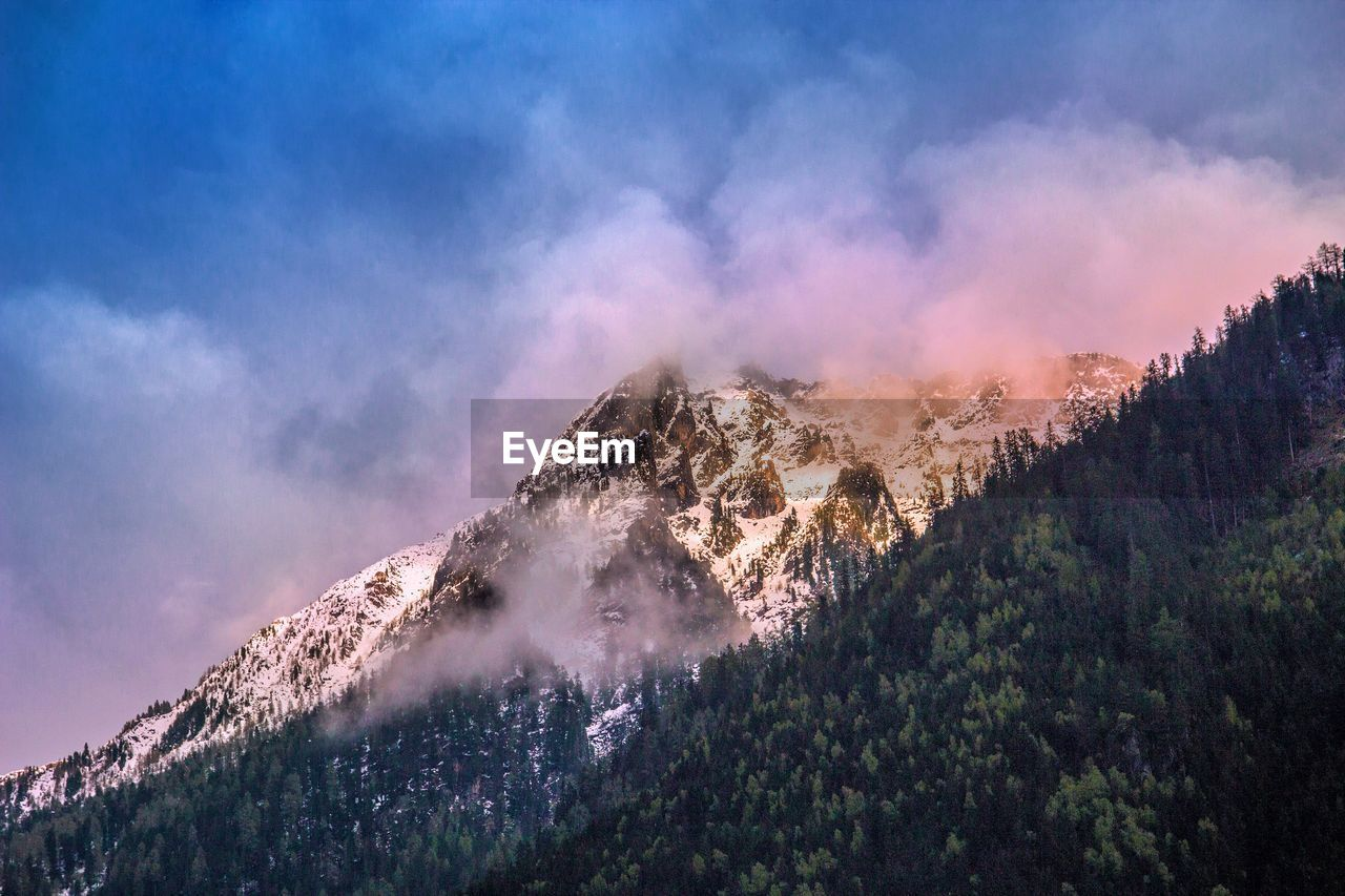 mountain, tree, beauty in nature, scenics - nature, plant, sky, tranquil scene, smoke - physical structure, non-urban scene, no people, cloud - sky, nature, tranquility, environment, geology, land, idyllic, outdoors, day, cold temperature, mountain peak, formation, power in nature