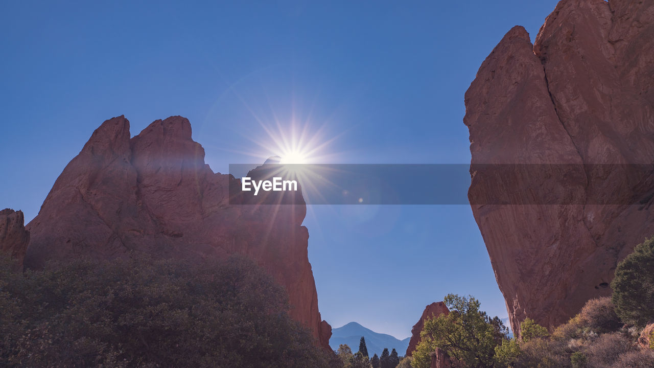 sky, mountain, rock, beauty in nature, sunlight, scenics - nature, rock formation, nature, tranquility, lens flare, tranquil scene, low angle view, rock - object, sun, non-urban scene, clear sky, solid, physical geography, sunbeam, mountain range, no people, outdoors, mountain peak, formation, bright, eroded