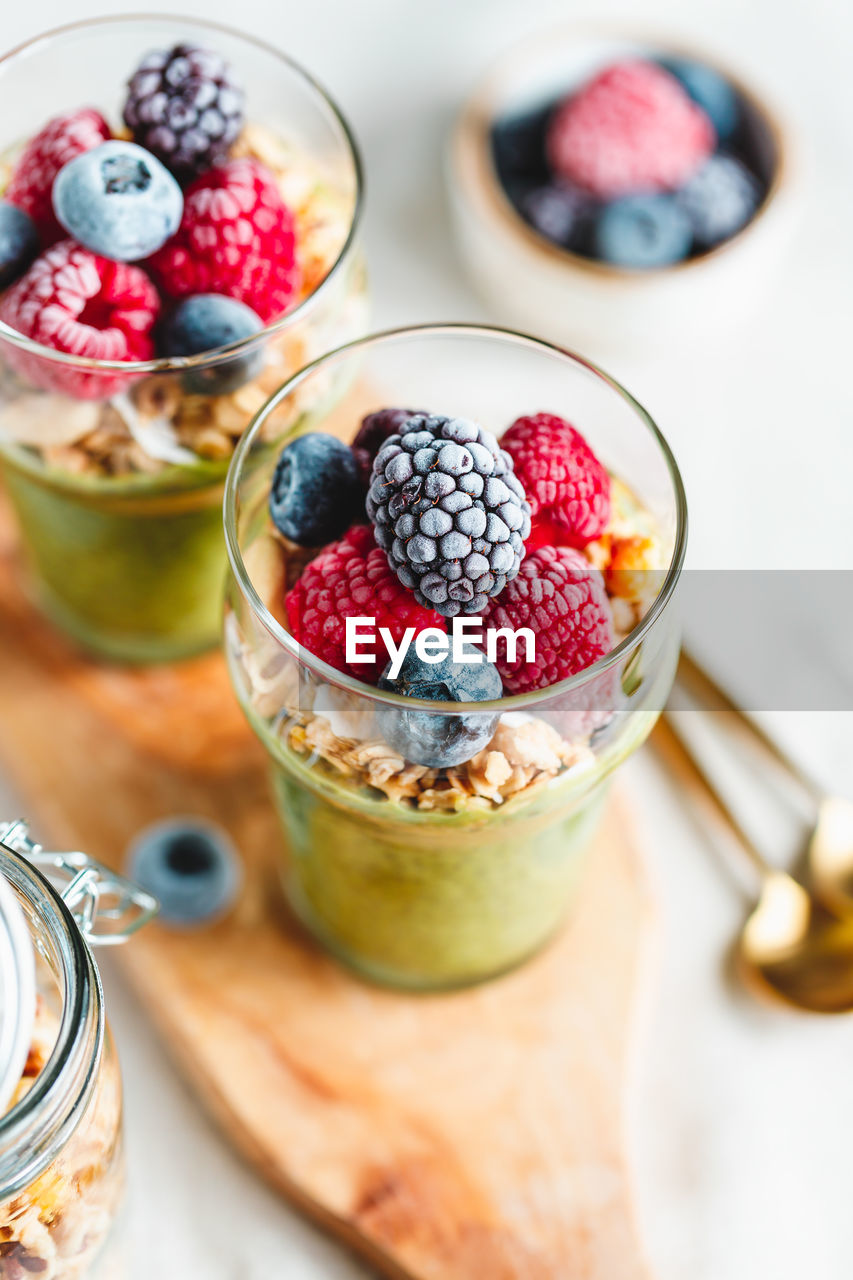 food and drink, food, healthy eating, freshness, fruit, berry fruit, wellbeing, table, blueberry, high angle view, spoon, bowl, raspberry, eating utensil, kitchen utensil, indoors, focus on foreground, no people, close-up, still life, glass, breakfast, yogurt, temptation