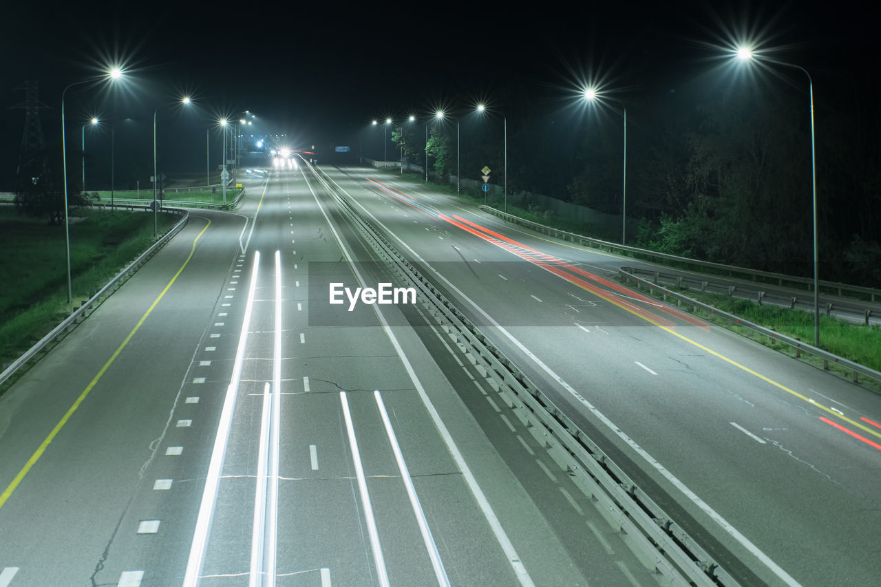 Country night track lit by lanterns. it shows streaks of light from the headlights of passing cars