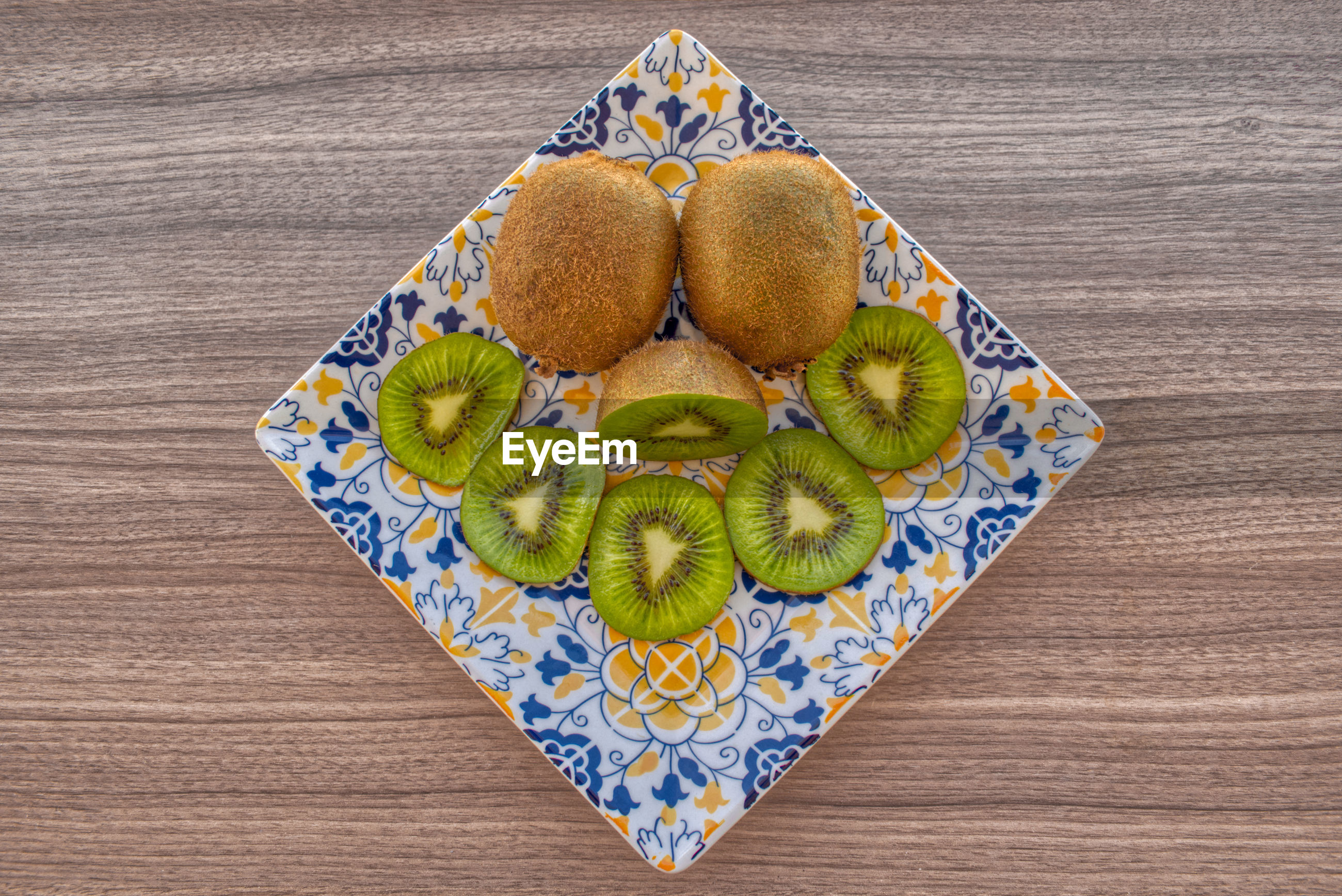 Fresh kiwi in a porcelain plate on wooden table