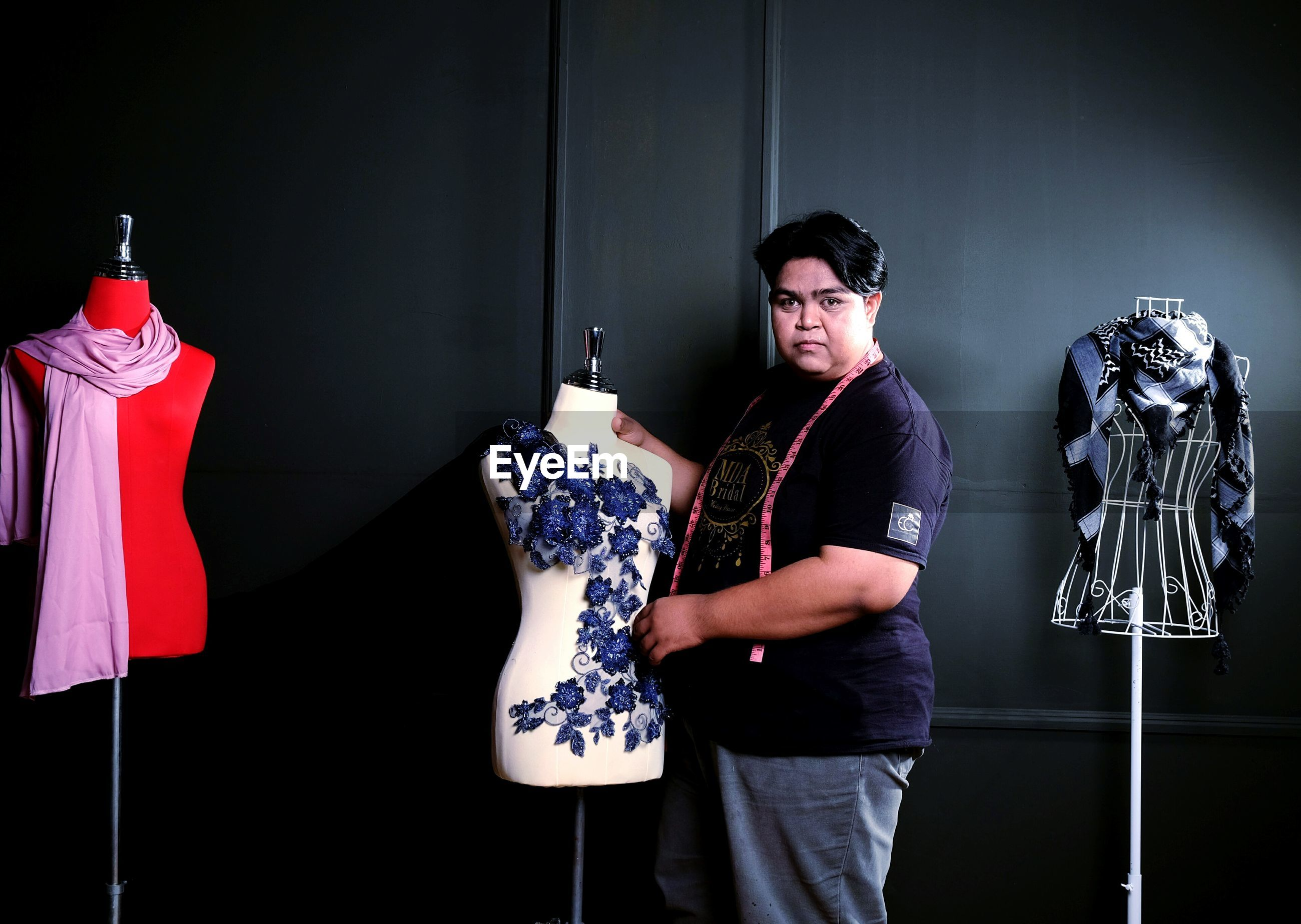 Portrait of designer holding mannequin while standing against wall