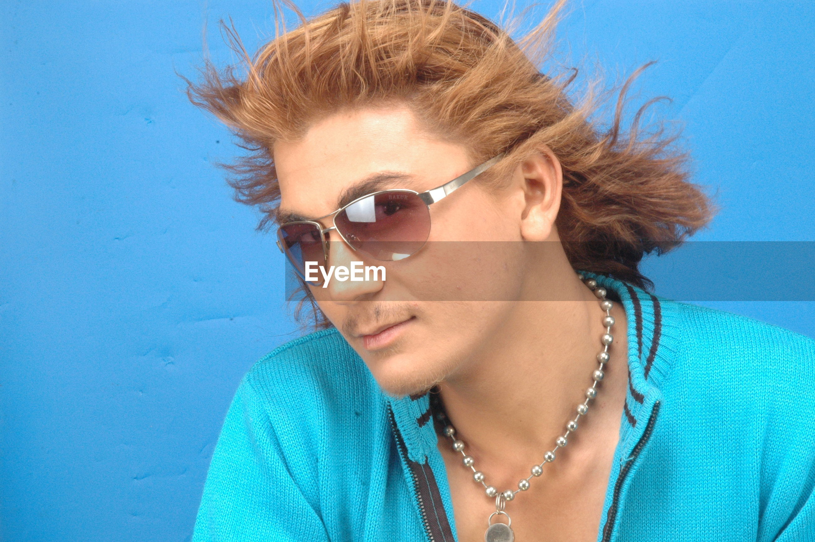 young adult, portrait, person, looking at camera, headshot, lifestyles, front view, leisure activity, casual clothing, young women, sunglasses, smiling, head and shoulders, blue, close-up, mid adult