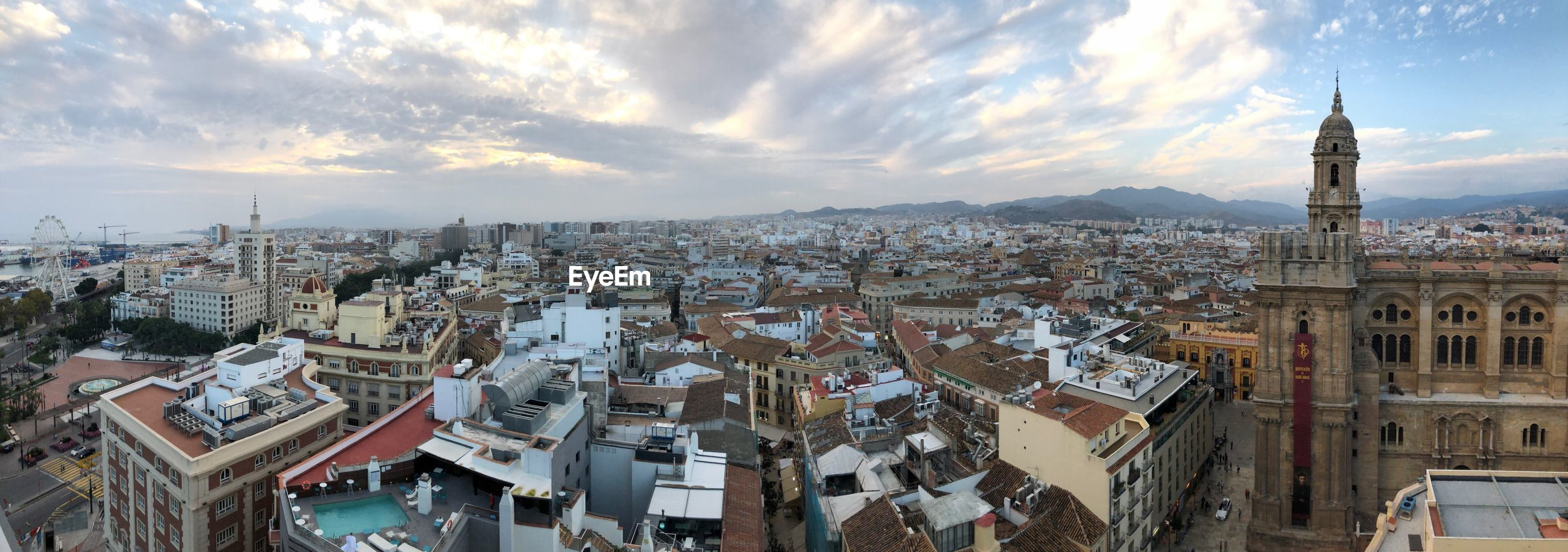 High angle view of buildings in city against cloudy sky in malaga