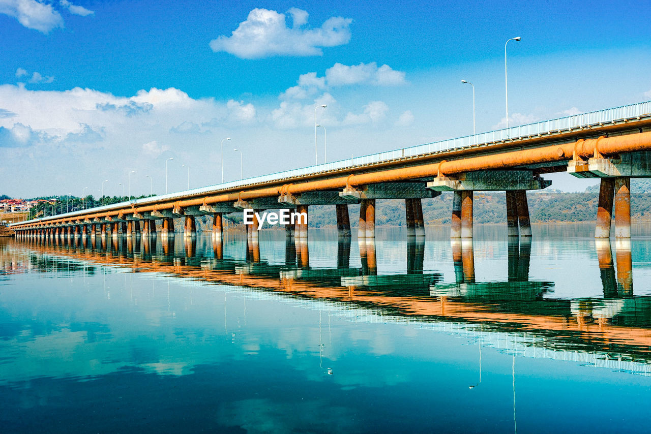 connection, bridge - man made structure, transportation, architecture, reflection, water, architectural column, sky, cloud - sky, built structure, day, waterfront, river, no people, outdoors, blue, symmetry, nature