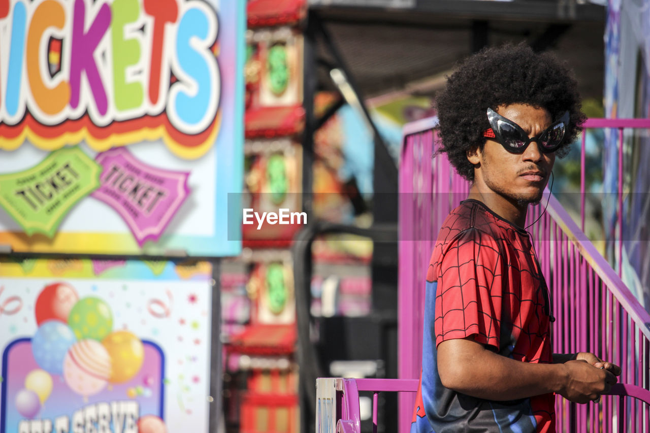 one person, real people, mid adult, mid adult men, black hair, standing, waist up, sunglasses, lifestyles, eyeglasses, front view, leisure activity, casual clothing, retail, multi colored, store, fashion, day, curly hair, indoors, young adult