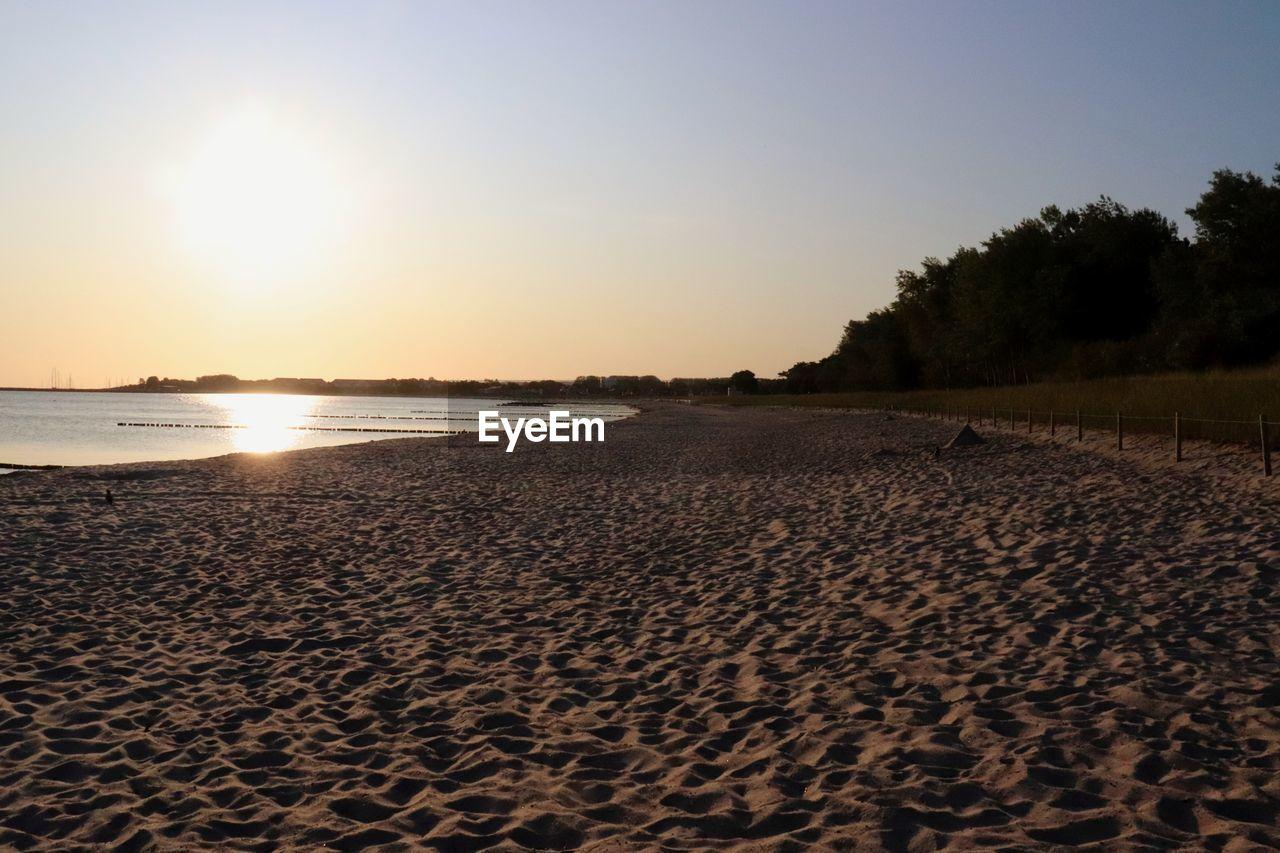 land, sky, sand, beach, beauty in nature, scenics - nature, tranquility, tranquil scene, nature, sunset, tree, sunlight, no people, water, sun, plant, non-urban scene, idyllic, outdoors