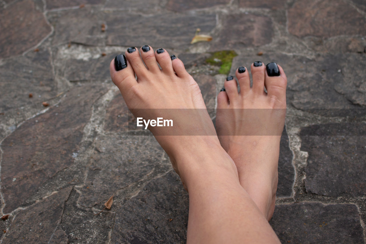 human body part, body part, low section, nail polish, human leg, barefoot, one person, nail, human foot, adult, women, day, relaxation, solid, personal perspective, lifestyles, rock, leisure activity, high angle view, outdoors, toenail, human toe, human limb