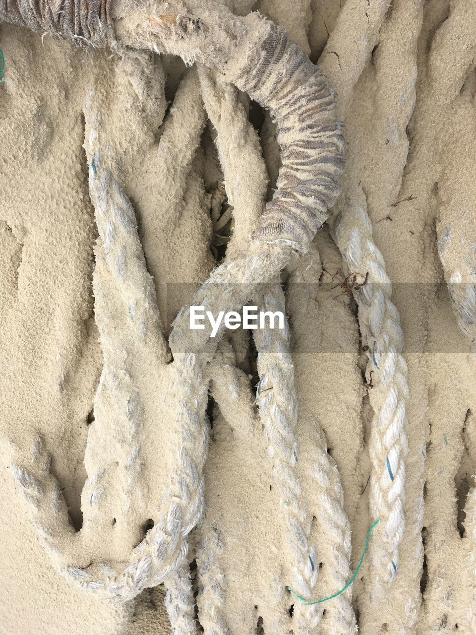 HIGH ANGLE VIEW OF ROPES ON SAND