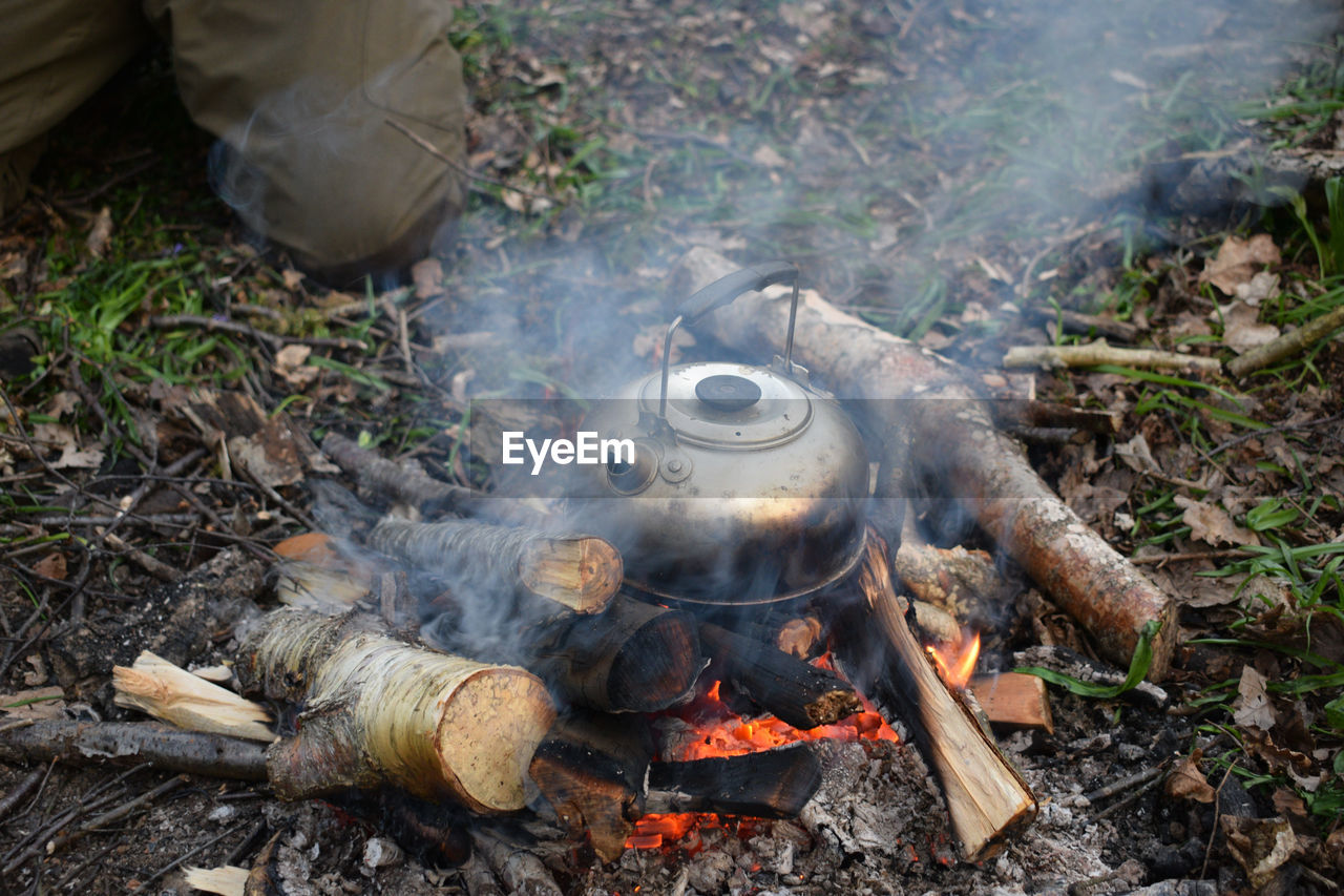 heat - temperature, fire - natural phenomenon, burning, fire, nature, day, smoke - physical structure, food and drink, household equipment, flame, kitchen utensil, wood, wood - material, food, firewood, preparation, log, high angle view, camping, bonfire, outdoors, campfire, camping stove, preparing food