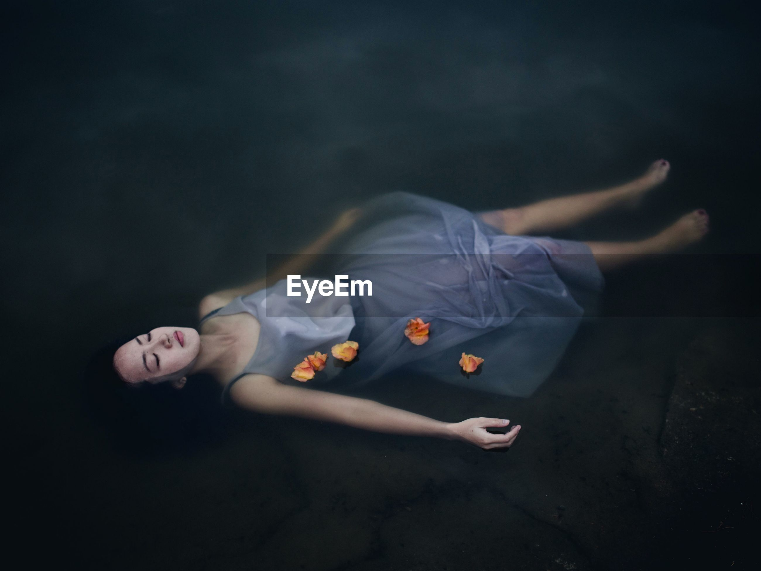 High angle view of young woman with eyes closed floating on lake