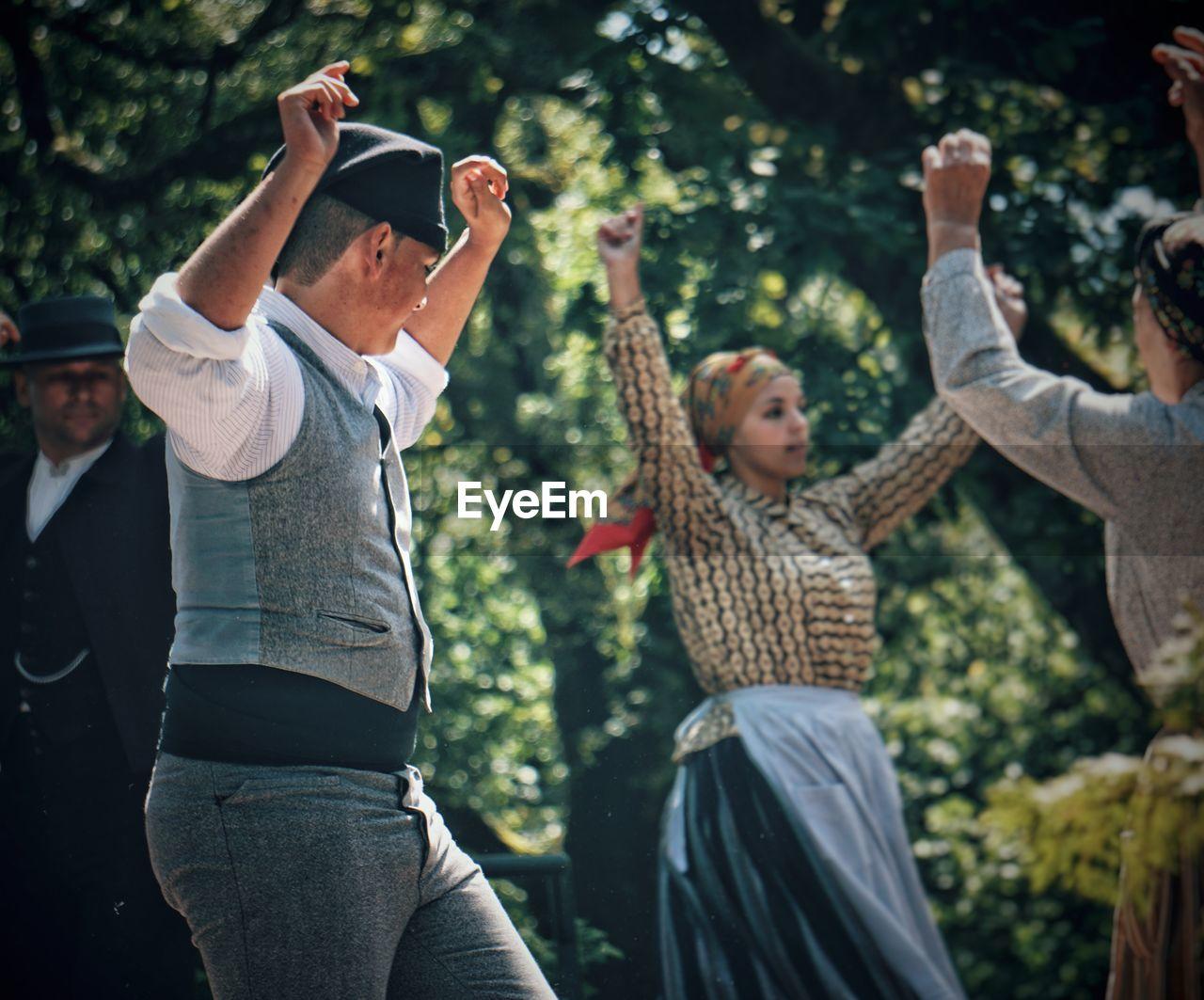 People dancing against trees in park