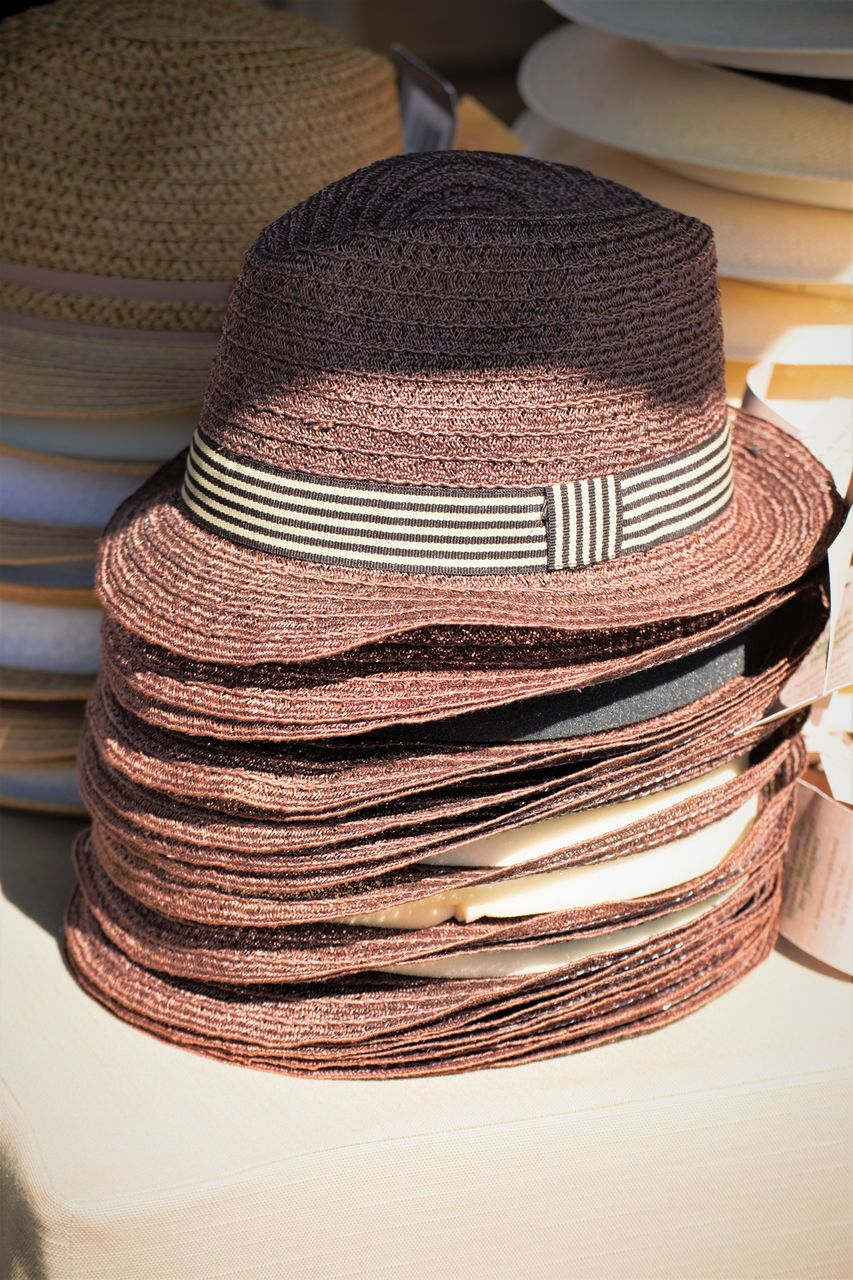hat, stack, indoors, still life, clothing, no people, table, focus on foreground, close-up, choice, for sale, business, pattern, retail, variation, brown, large group of objects, sun hat, straw hat, day, personal accessory