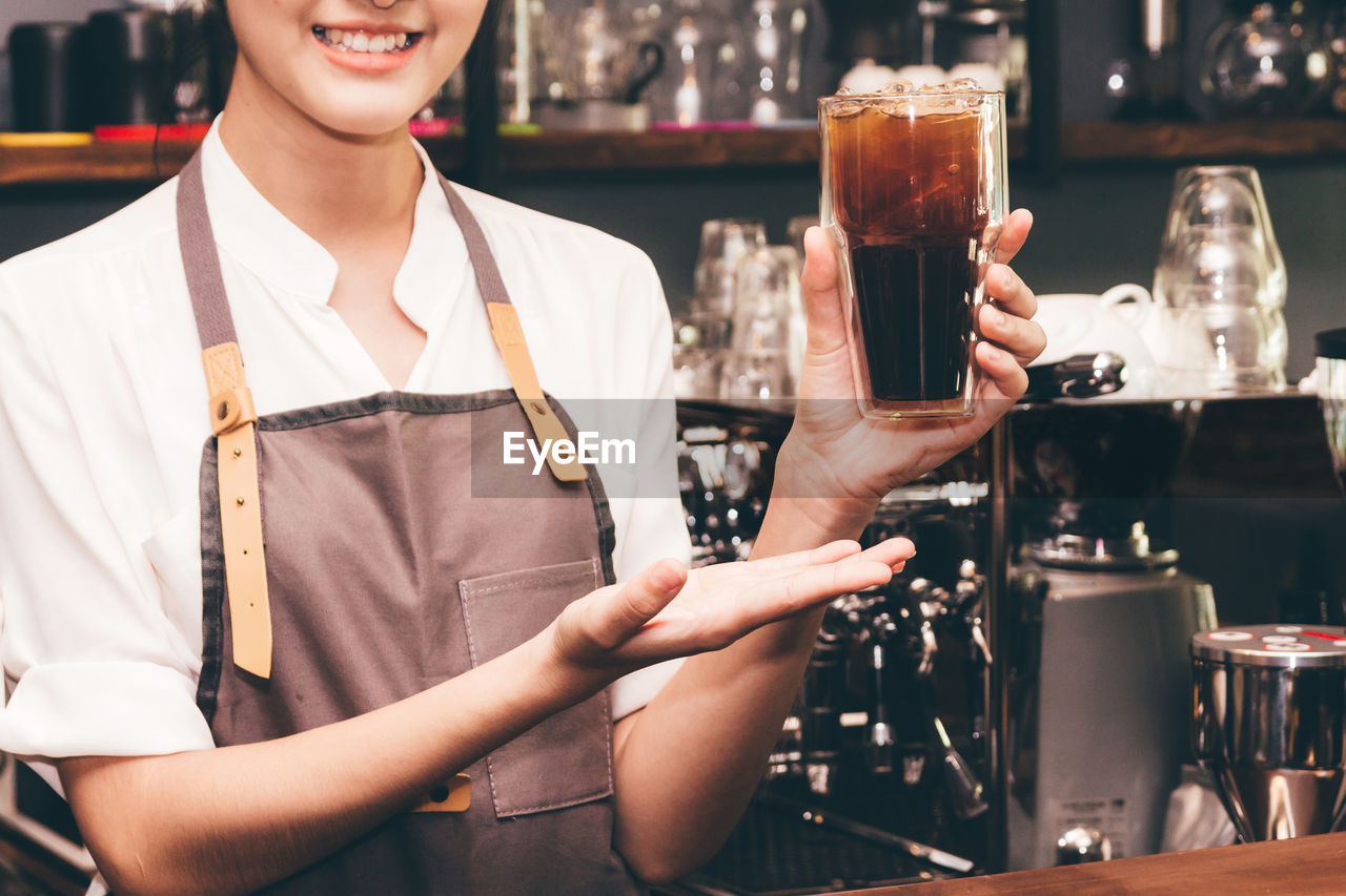 drink, refreshment, food and drink, alcohol, smiling, bar - drink establishment, occupation, business, focus on foreground, holding, front view, service, standing, glass, adult, real people, serving food and drinks, women, food and drink industry, drinking glass, bar counter, bartender