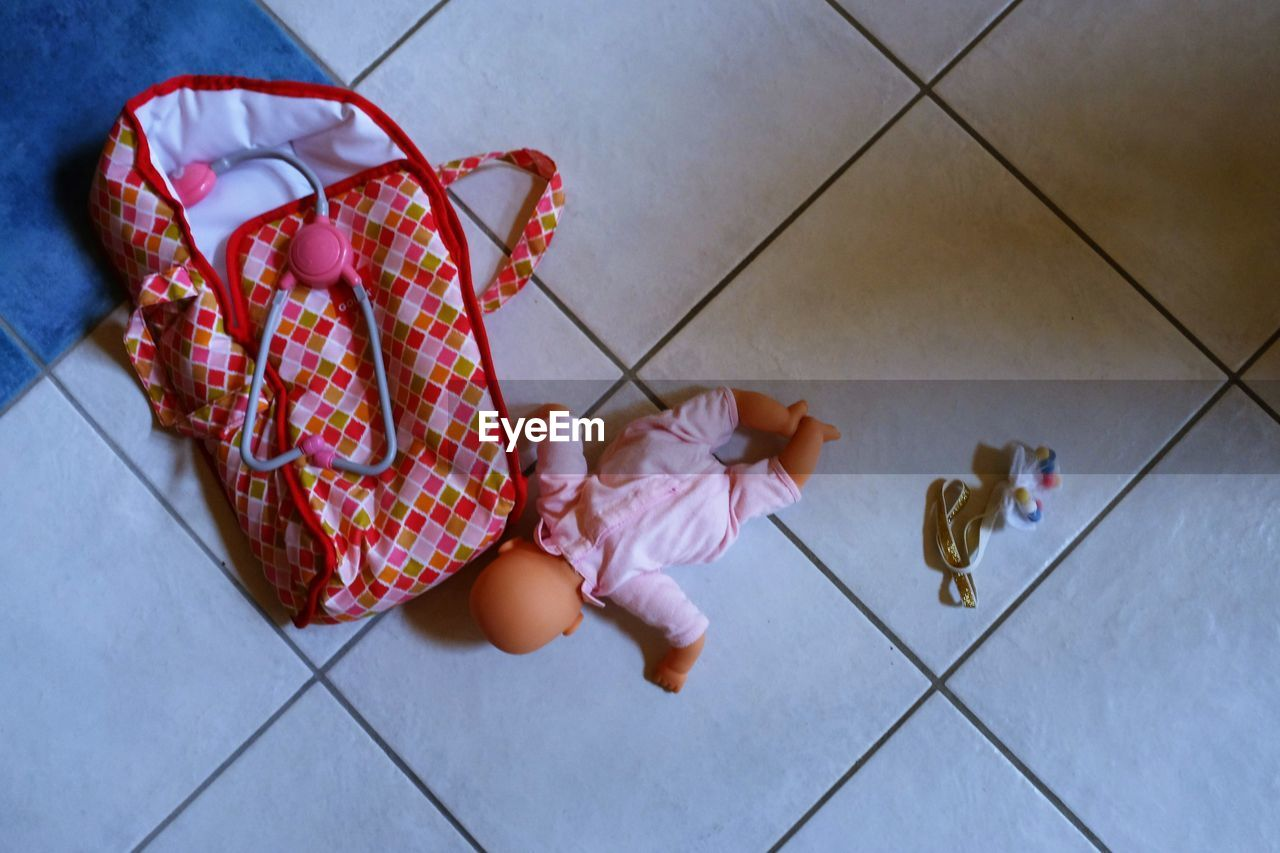 High Angle View Of Doll And Toys On Tiled Floor At Home
