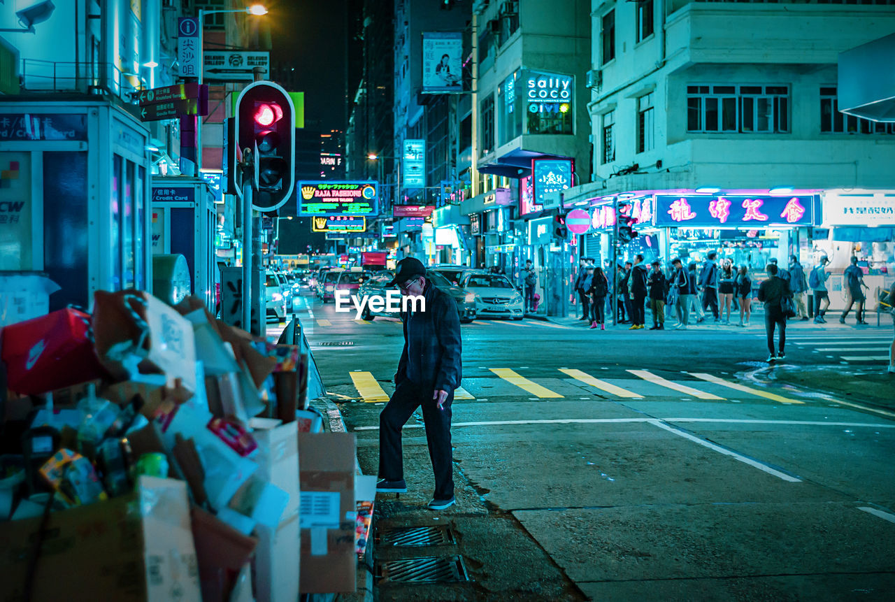 city, building exterior, architecture, sign, street, road, illuminated, walking, built structure, real people, city life, communication, transportation, group of people, crossing, symbol, road marking, people, night, crosswalk, city street, light