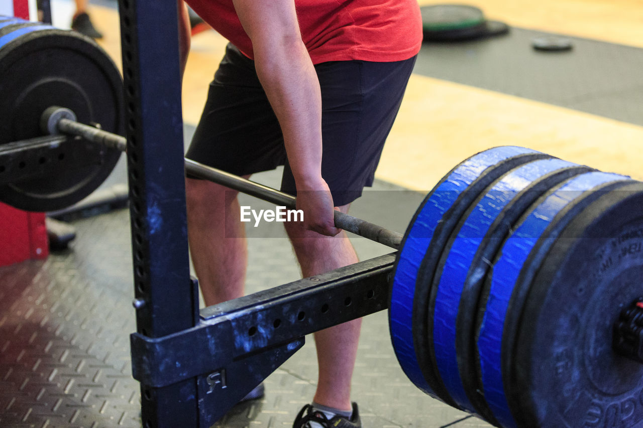 Mid Section Of A Man Exercising With Barbell