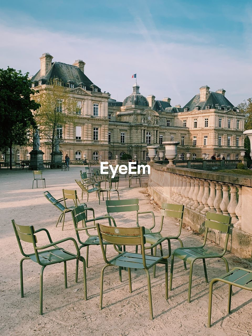 EMPTY CHAIRS AND TABLE BY BUILDINGS AGAINST SKY