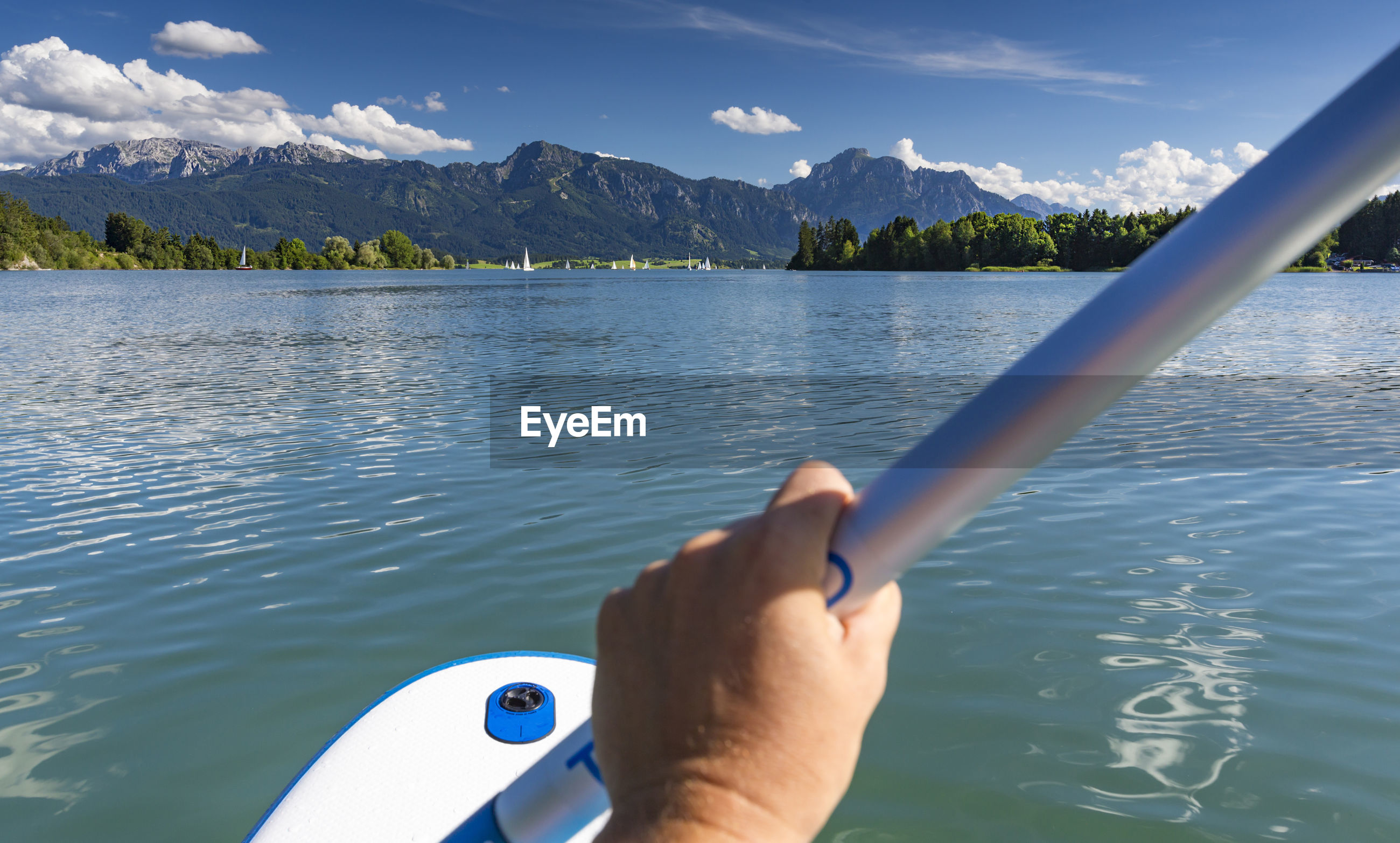Cropped image of person holding pole in boat on lake