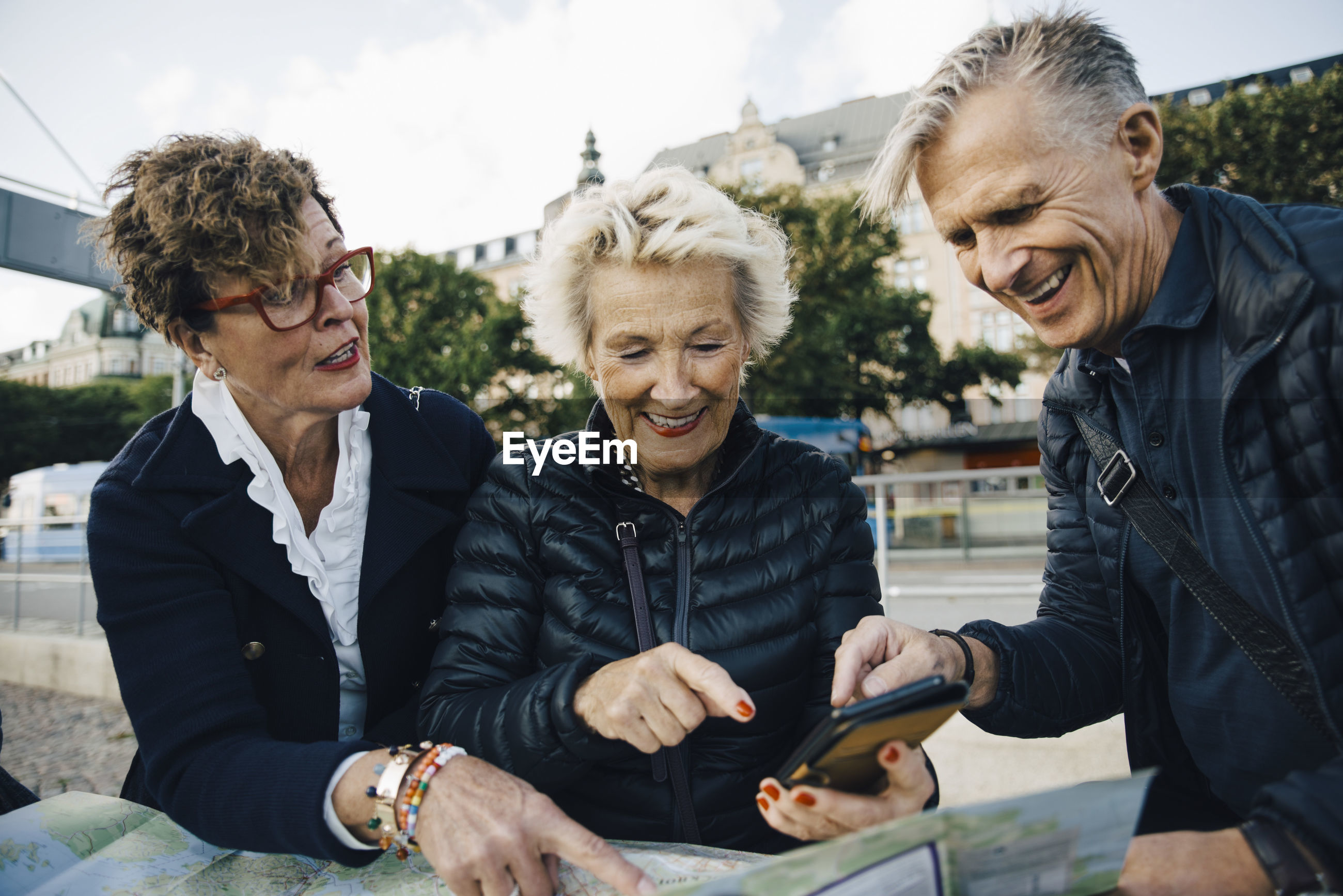 Senior male and female friends with map and mobile phone in city