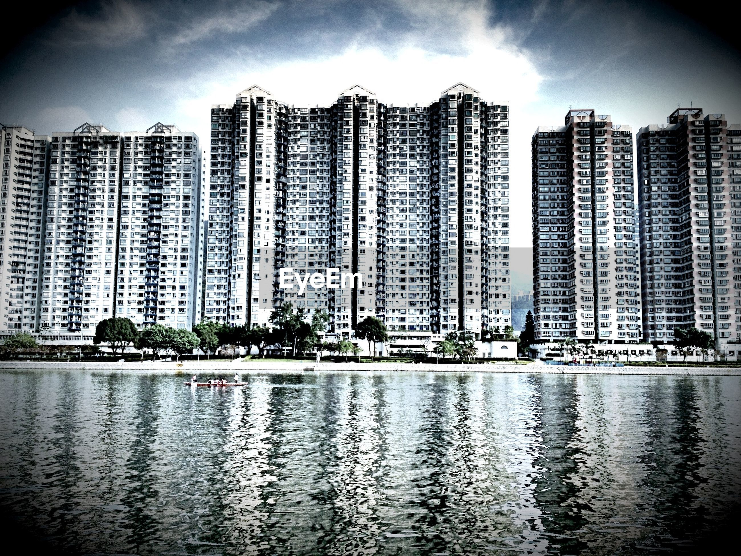 River in front of buildings against cloudy sky
