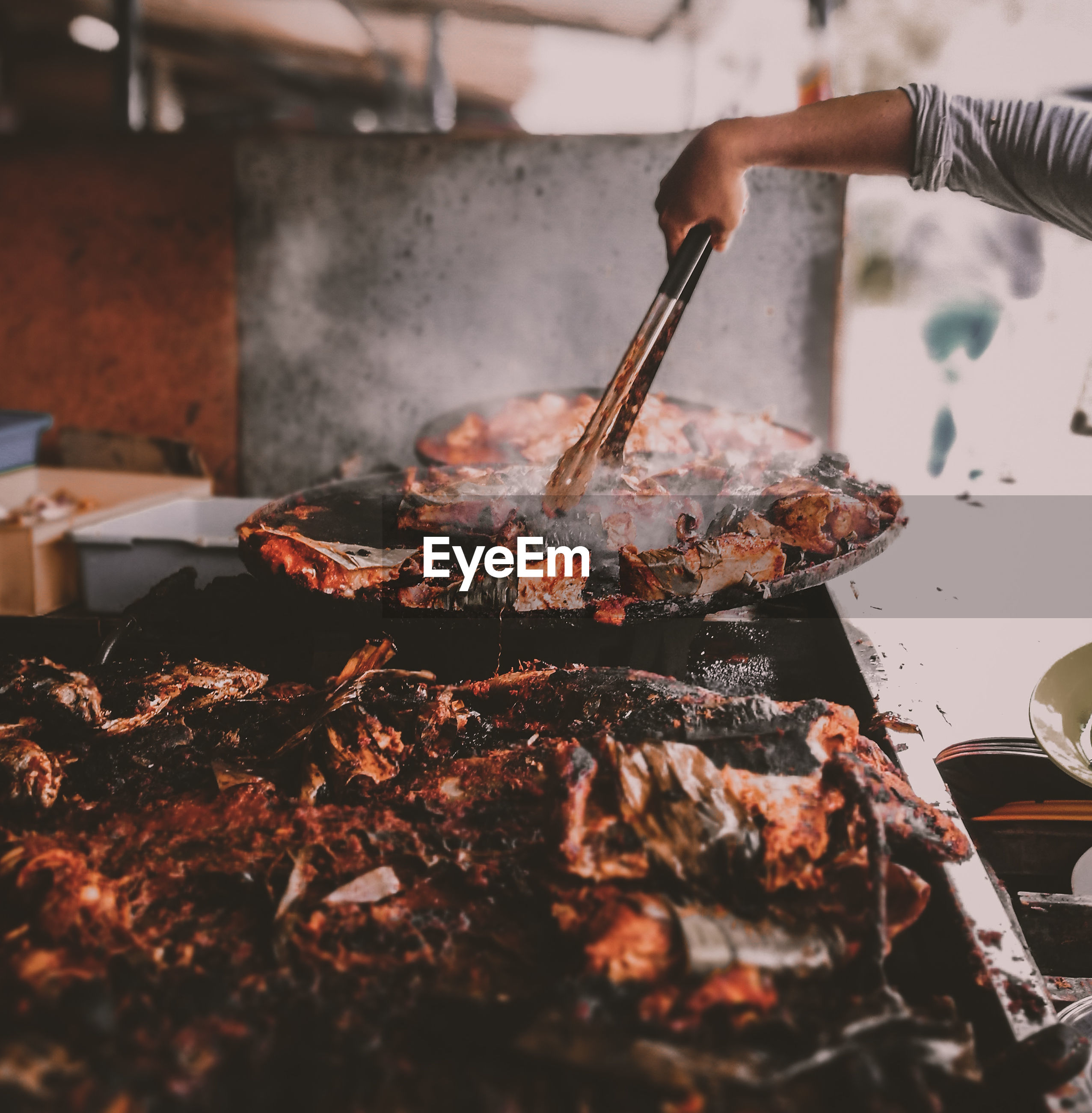 Cropped image of person roasting meat at market stall