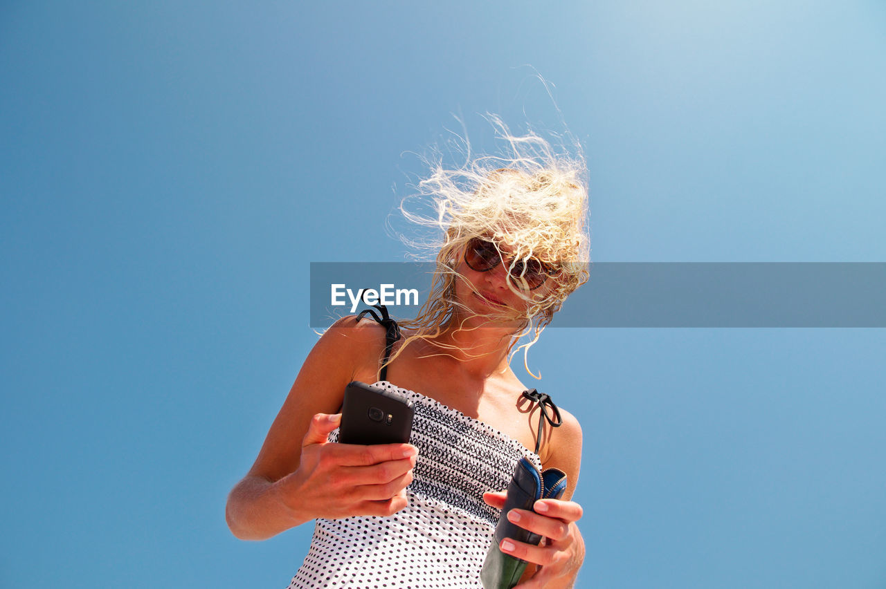 Low Angle View Of Woman Using Mobile Phone Against Clear Blue Sky