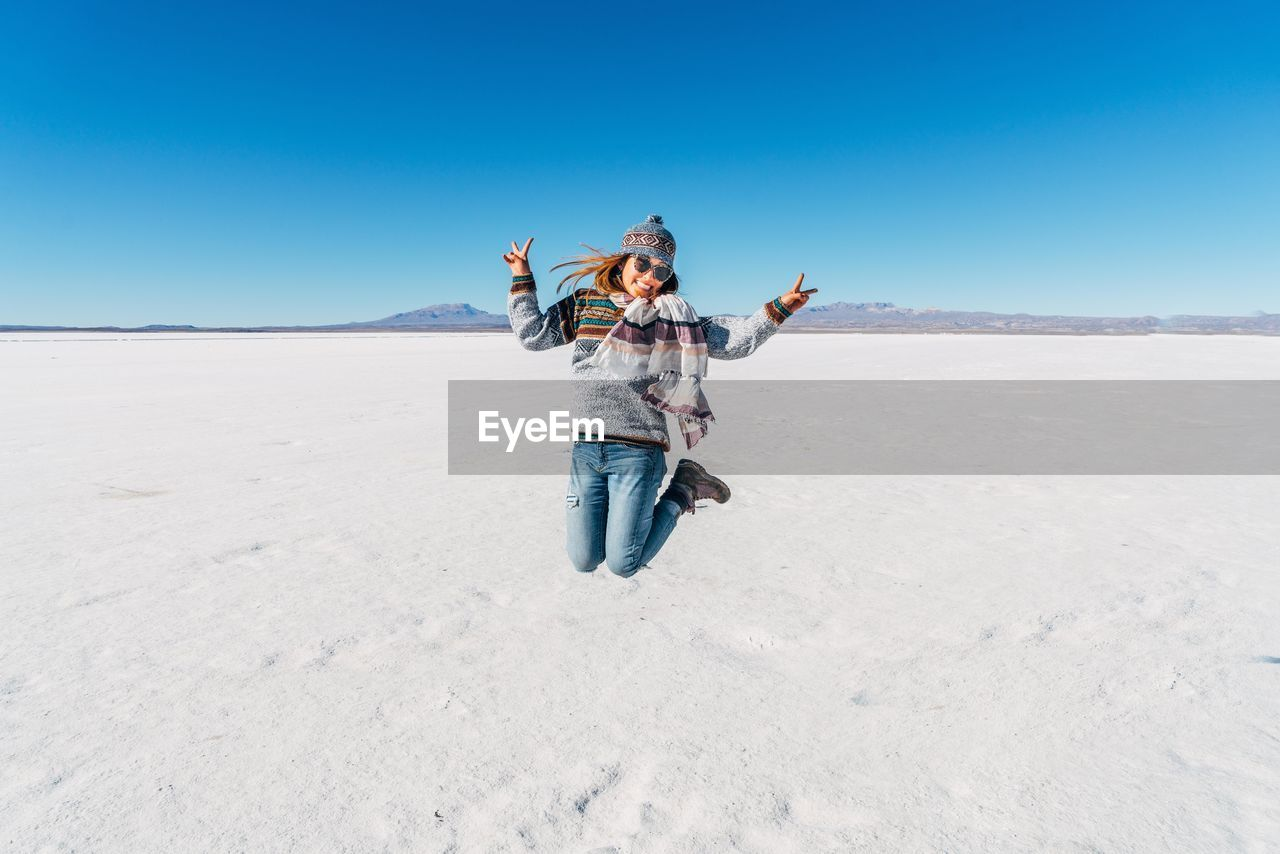 Portrait Of Young Woman Jumping On Desert Against Clear Blue Sky