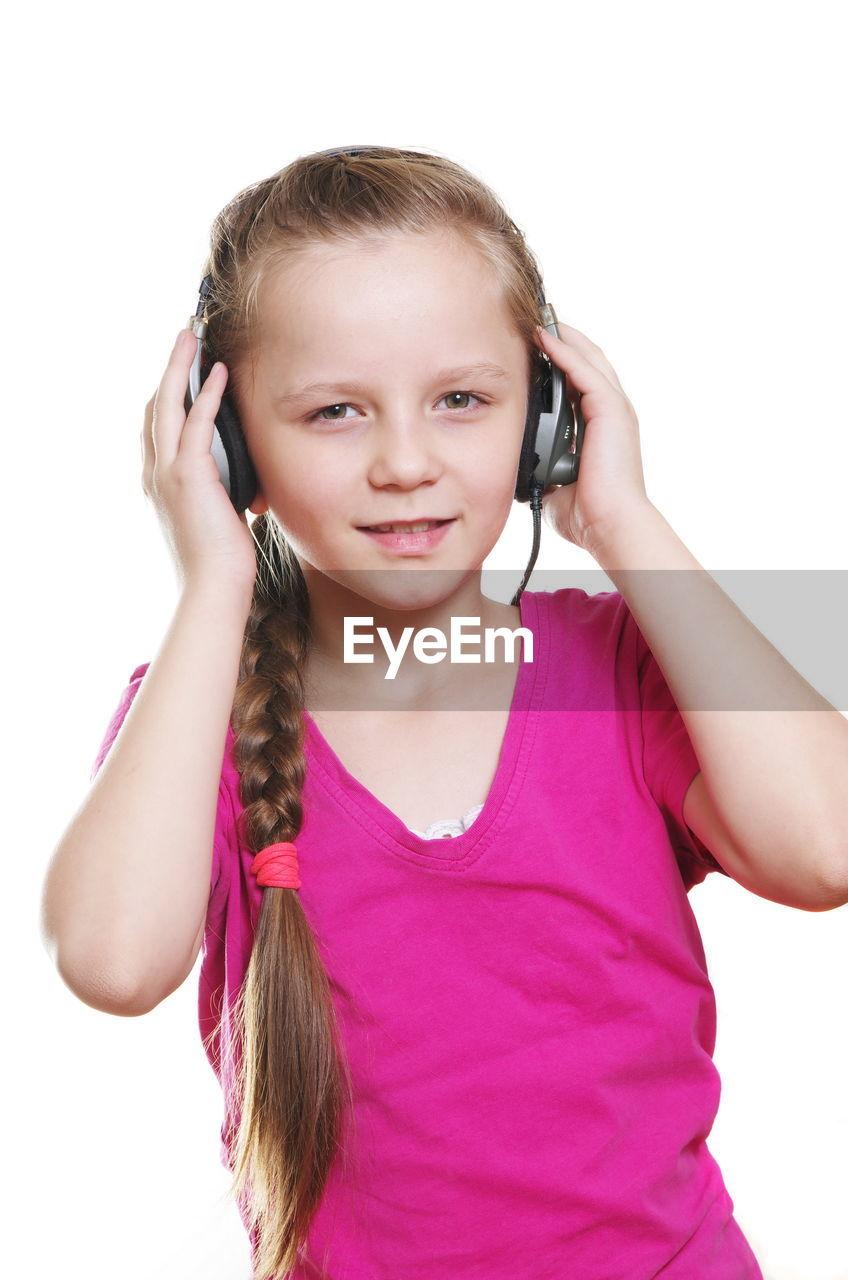 Portrait Of Cute Girl Listening Music Through Headphones Against White Background