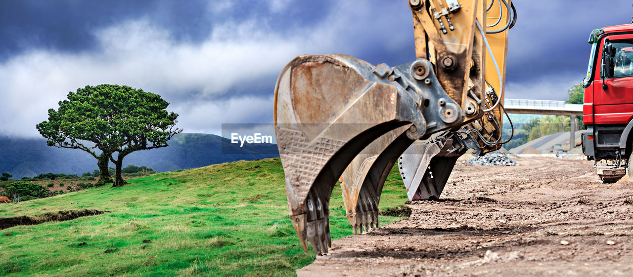 Earth Mover On Field Against Sky