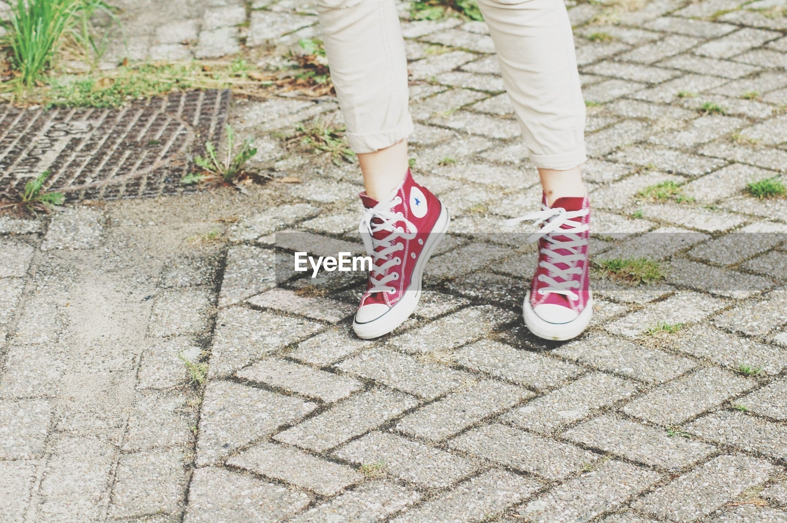 high angle view, text, cobblestone, sidewalk, street, footpath, paving stone, communication, day, low section, outdoors, shoe, safety, western script, protection, red, sunlight, ground, pattern, close-up
