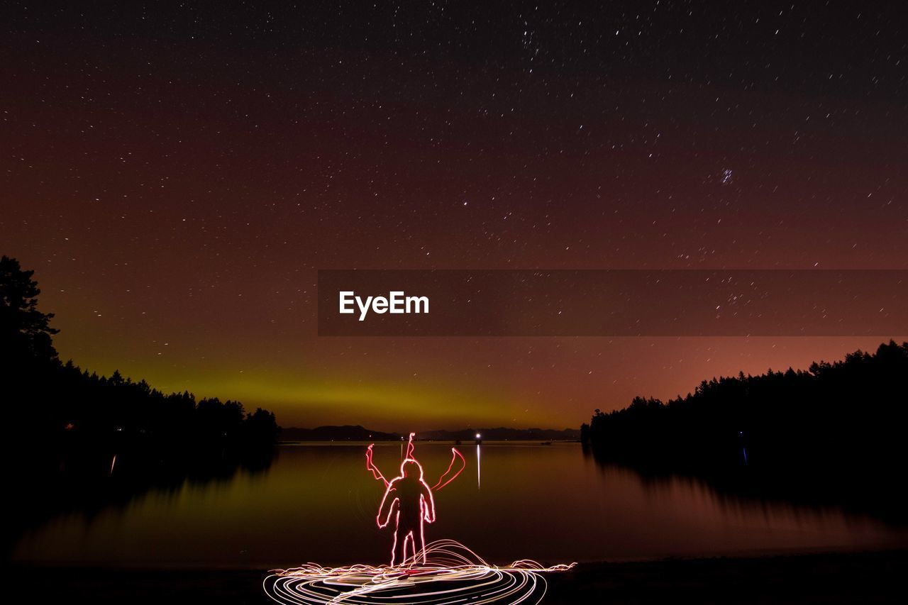 Light Painting By Lake Against Star Field At Night