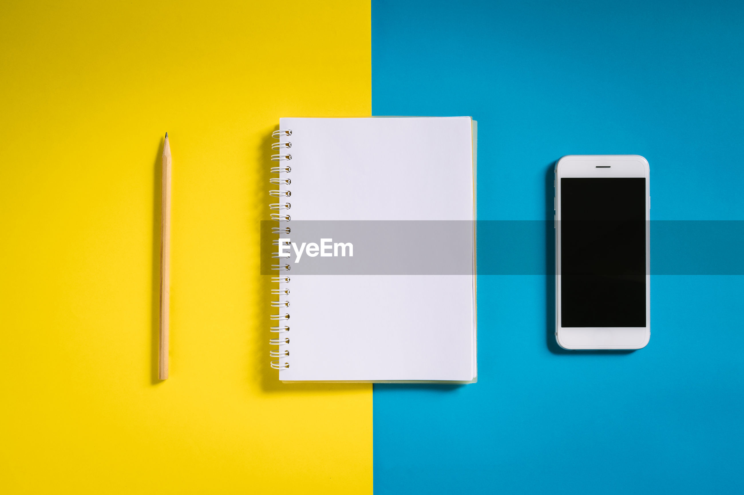 High angle view of mobile phone with note pad and pencil over colored background