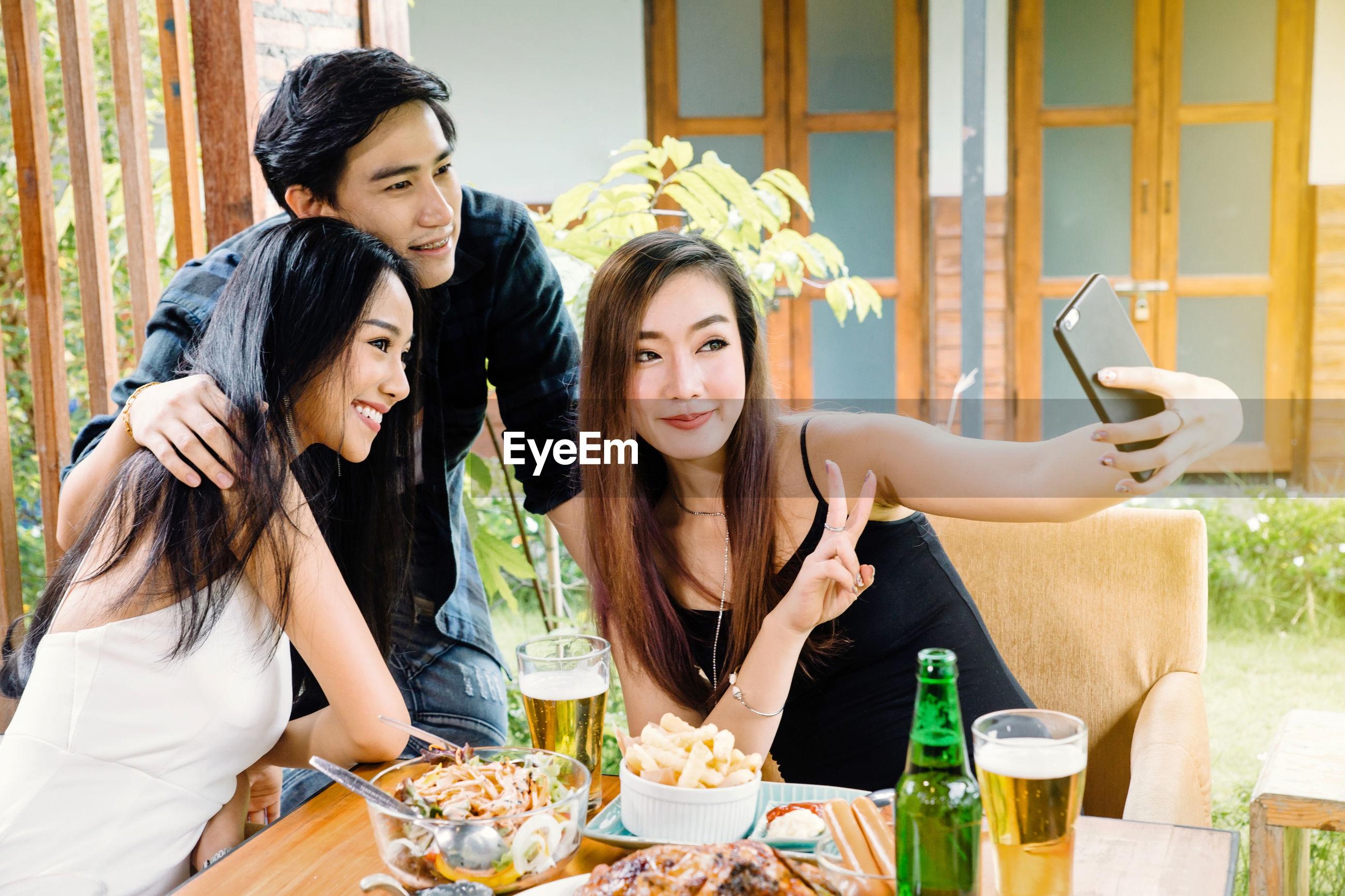 Friends taking selfie in restaurant