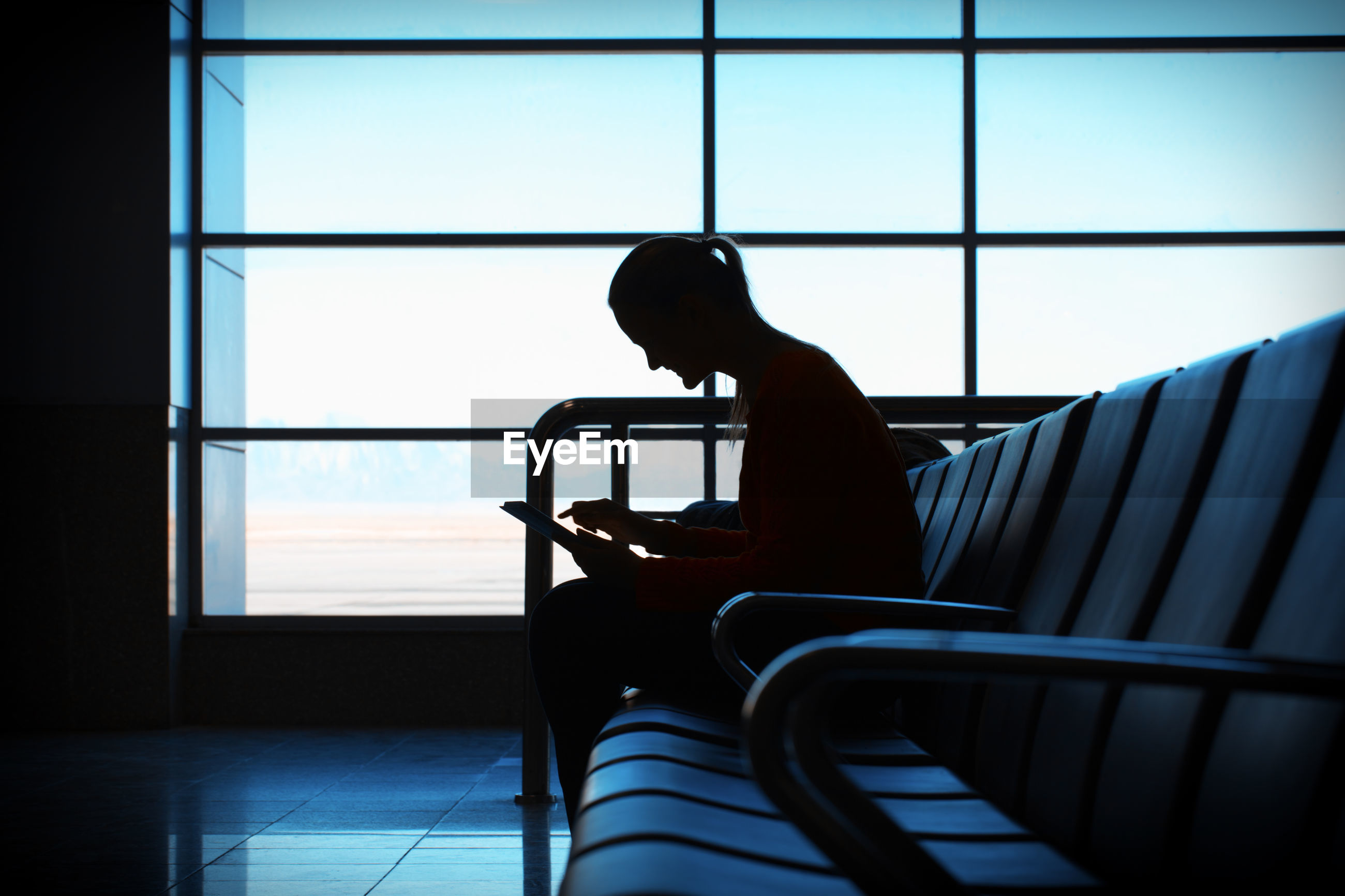 Woman using digital tablet while sitting on chair in airport lobby