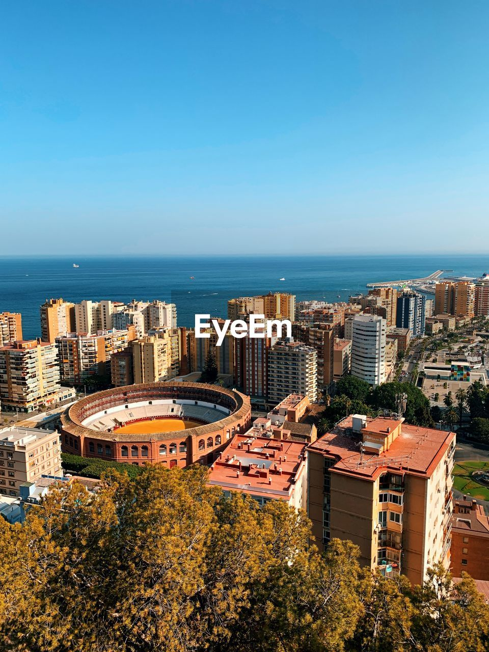High angle view of buildings and sea against clear blue sky