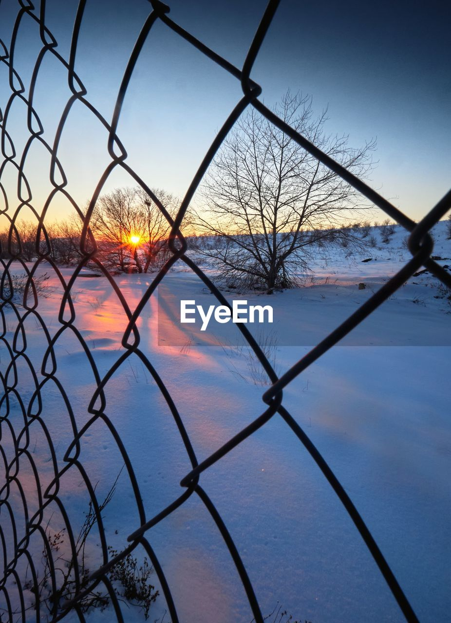 LAKE SEEN THROUGH CHAINLINK FENCE DURING WINTER