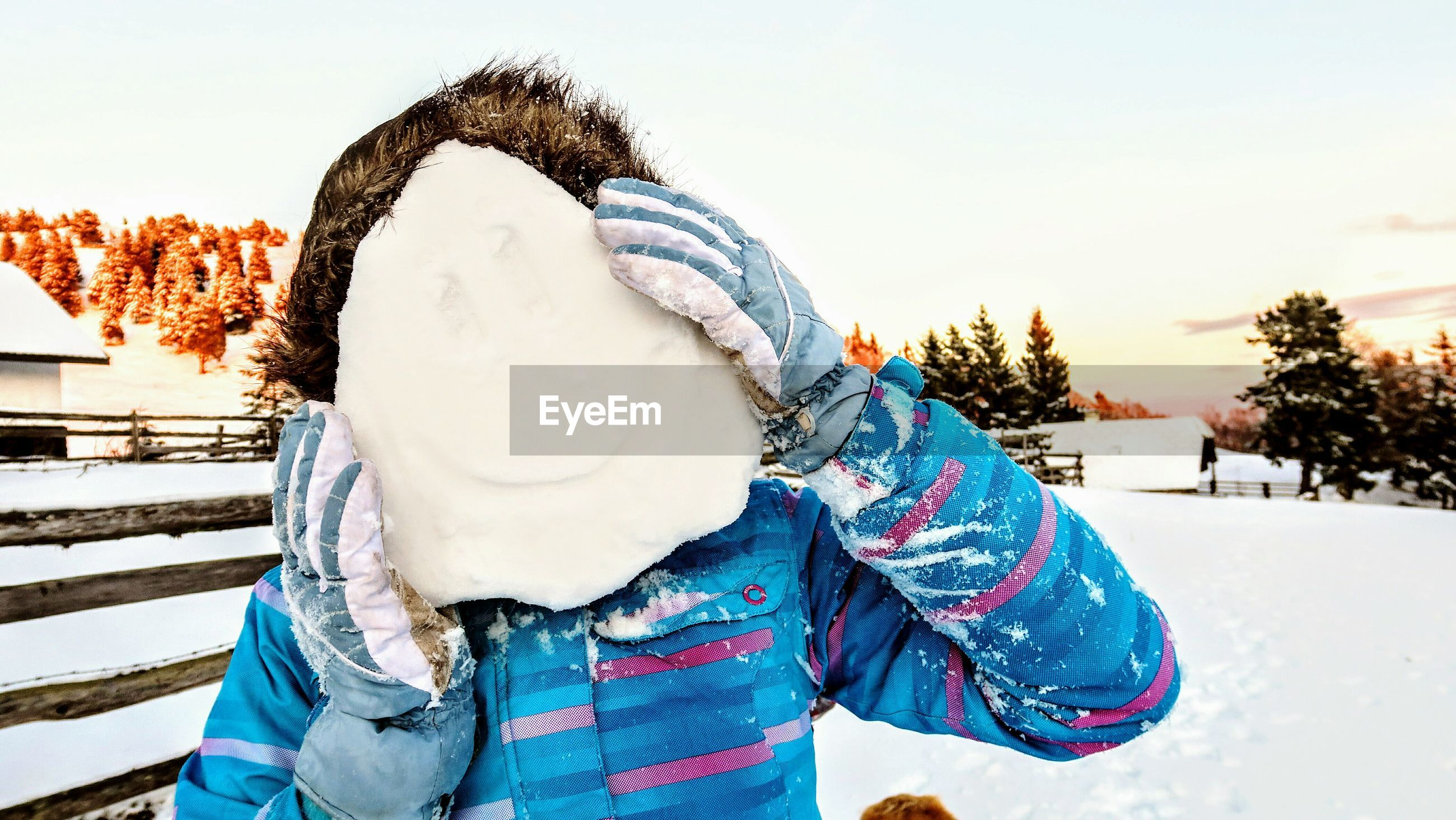Close-up of woman holding snow while standing on field during winter