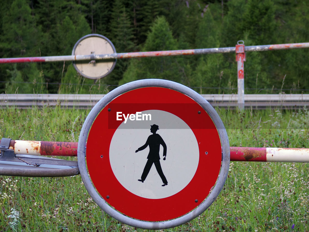 sign, communication, shape, human representation, geometric shape, circle, representation, warning sign, day, red, plant, nature, safety, metal, close-up, male likeness, no people, grass, road sign, field, outdoors