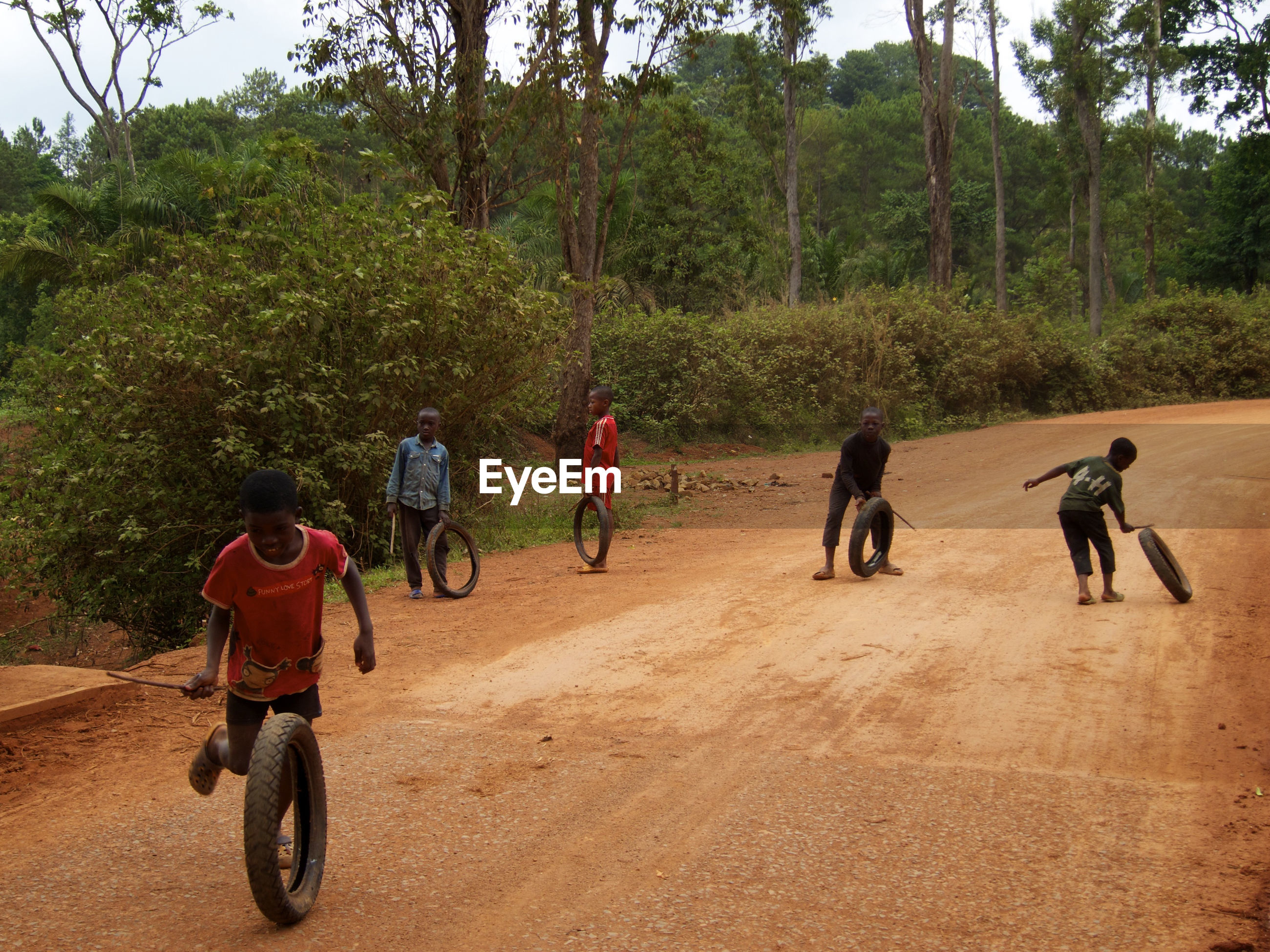 REAR VIEW OF PEOPLE PLAYING ON THE ROAD