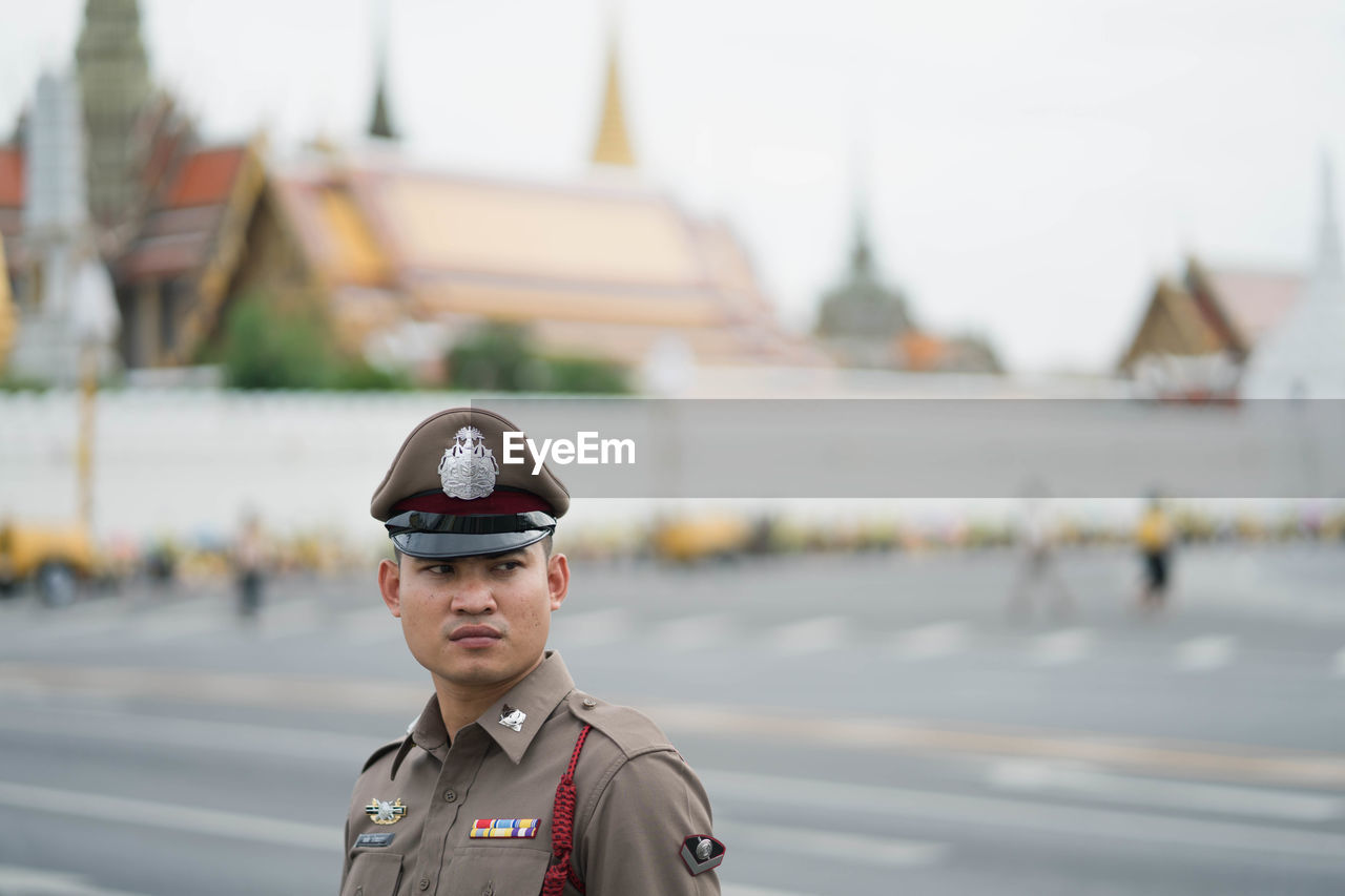 portrait, architecture, one person, focus on foreground, young adult, built structure, looking at camera, building exterior, clothing, standing, day, real people, headshot, uniform, water, government, building, men