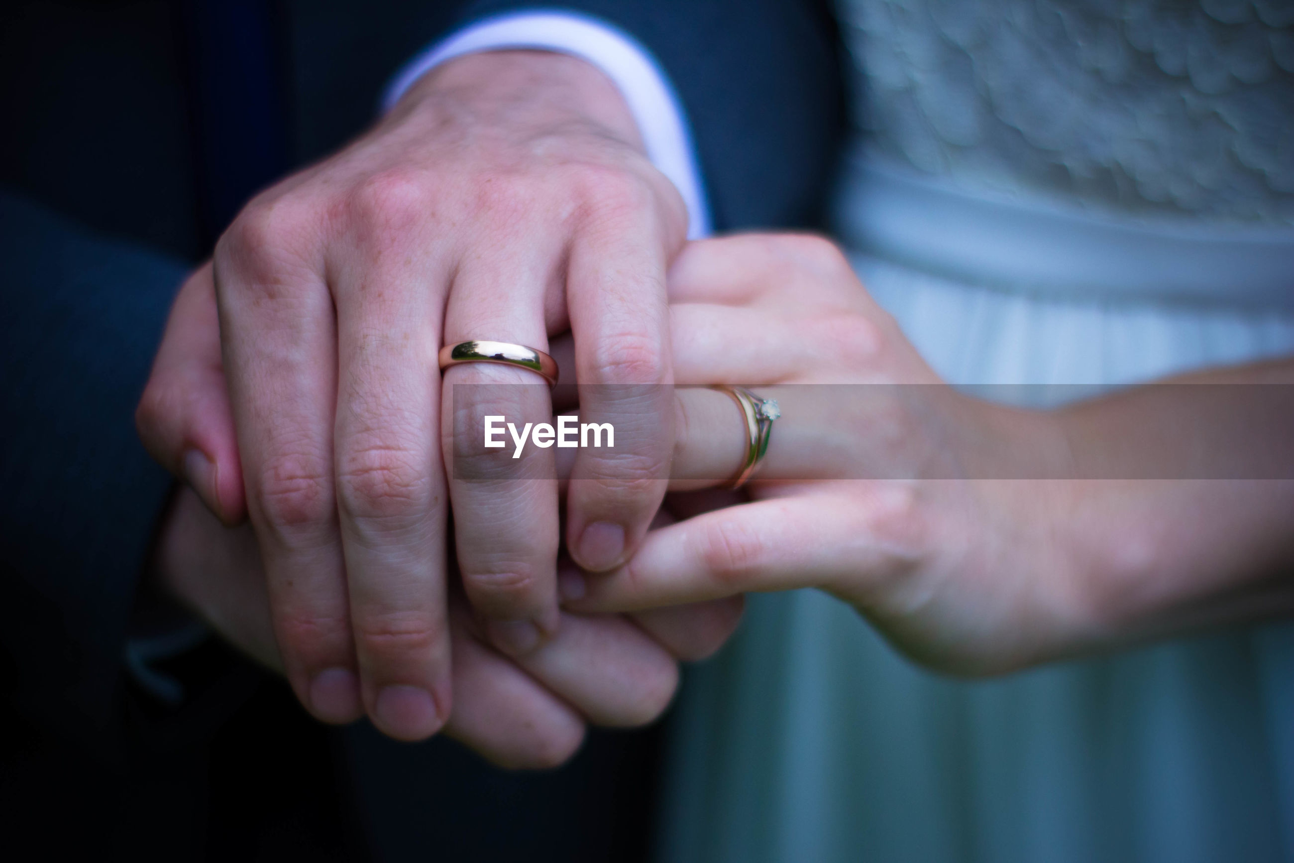 Extreme close up of wedding rings on couple