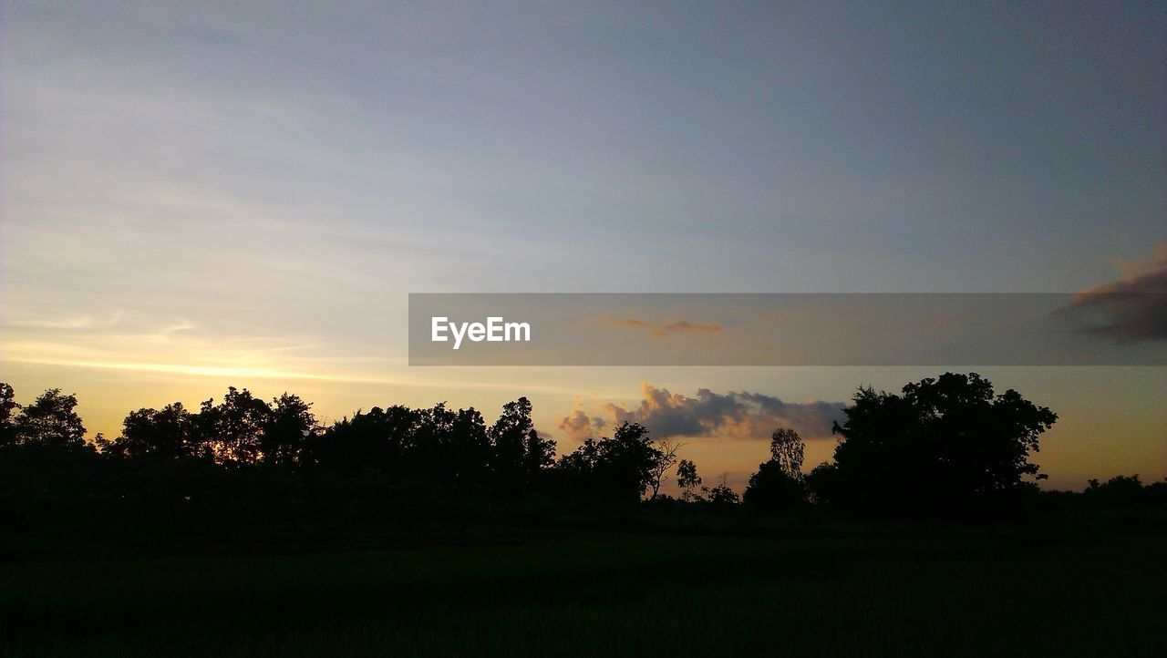 SCENIC VIEW OF SILHOUETTE FIELD AGAINST SKY AT SUNSET