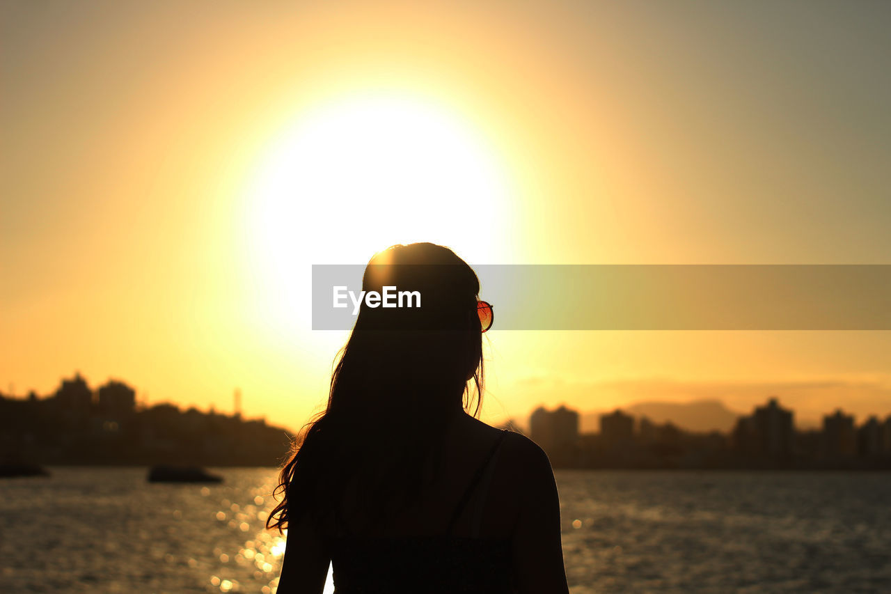 Silhouette of woman looking at sunset