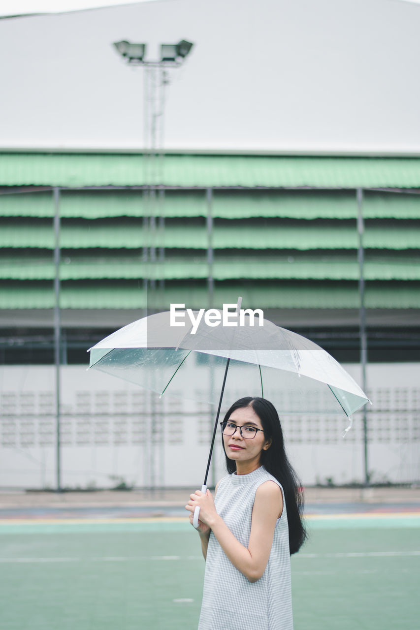 real people, one person, smiling, umbrella, lifestyles, young adult, holding, portrait, women, happiness, leisure activity, standing, young women, front view, casual clothing, adult, architecture, focus on foreground, outdoors, rain, beautiful woman, hairstyle