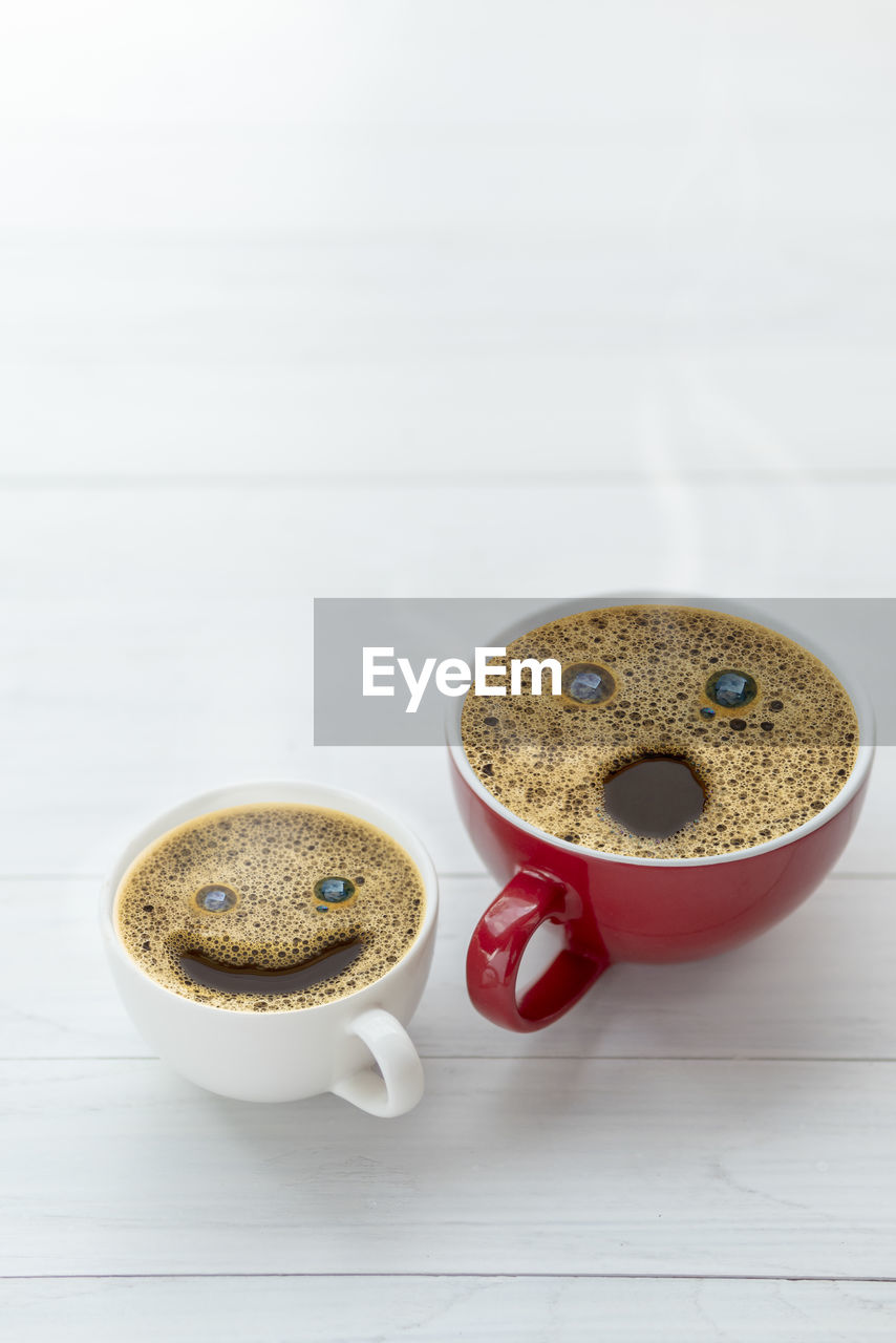 CLOSE-UP OF COFFEE CUP AND COOKIES
