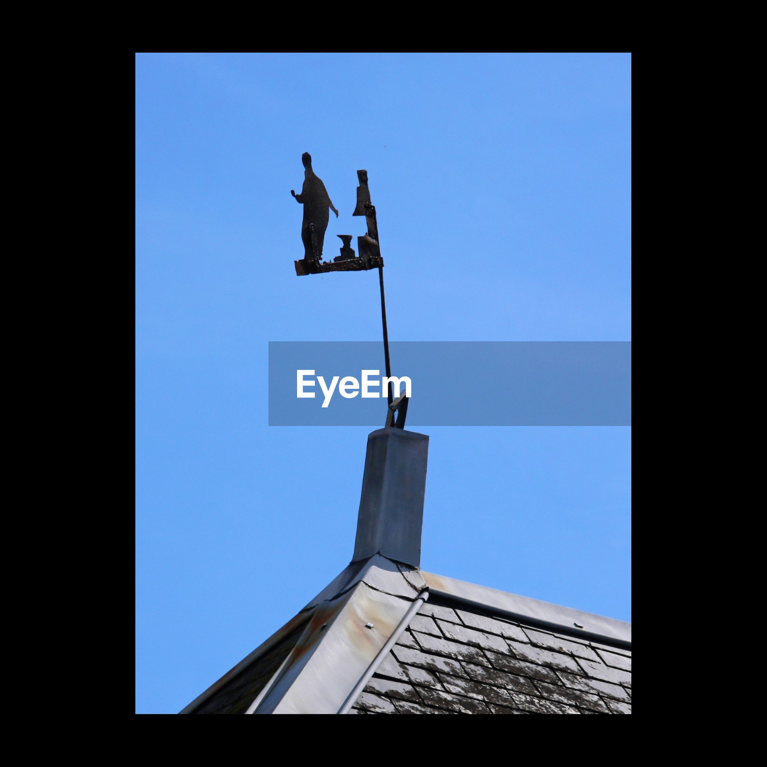 low angle view, clear sky, silhouette, copy space, built structure, architecture, transfer print, building exterior, blue, auto post production filter, men, mid-air, day, outdoors, flying, sky, travel, leisure activity, lifestyles