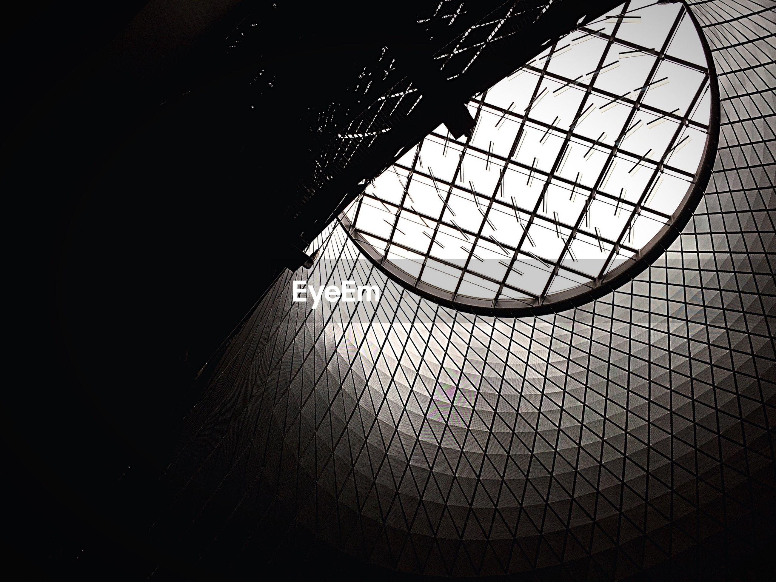 indoors, architecture, built structure, pattern, ceiling, window, low angle view, geometric shape, design, skylight, glass - material, building, wall - building feature, no people, architectural feature, metal, day, shadow, circle, sunlight
