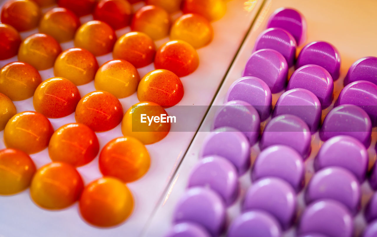 HIGH ANGLE VIEW OF MULTI COLORED CANDIES IN PLATE